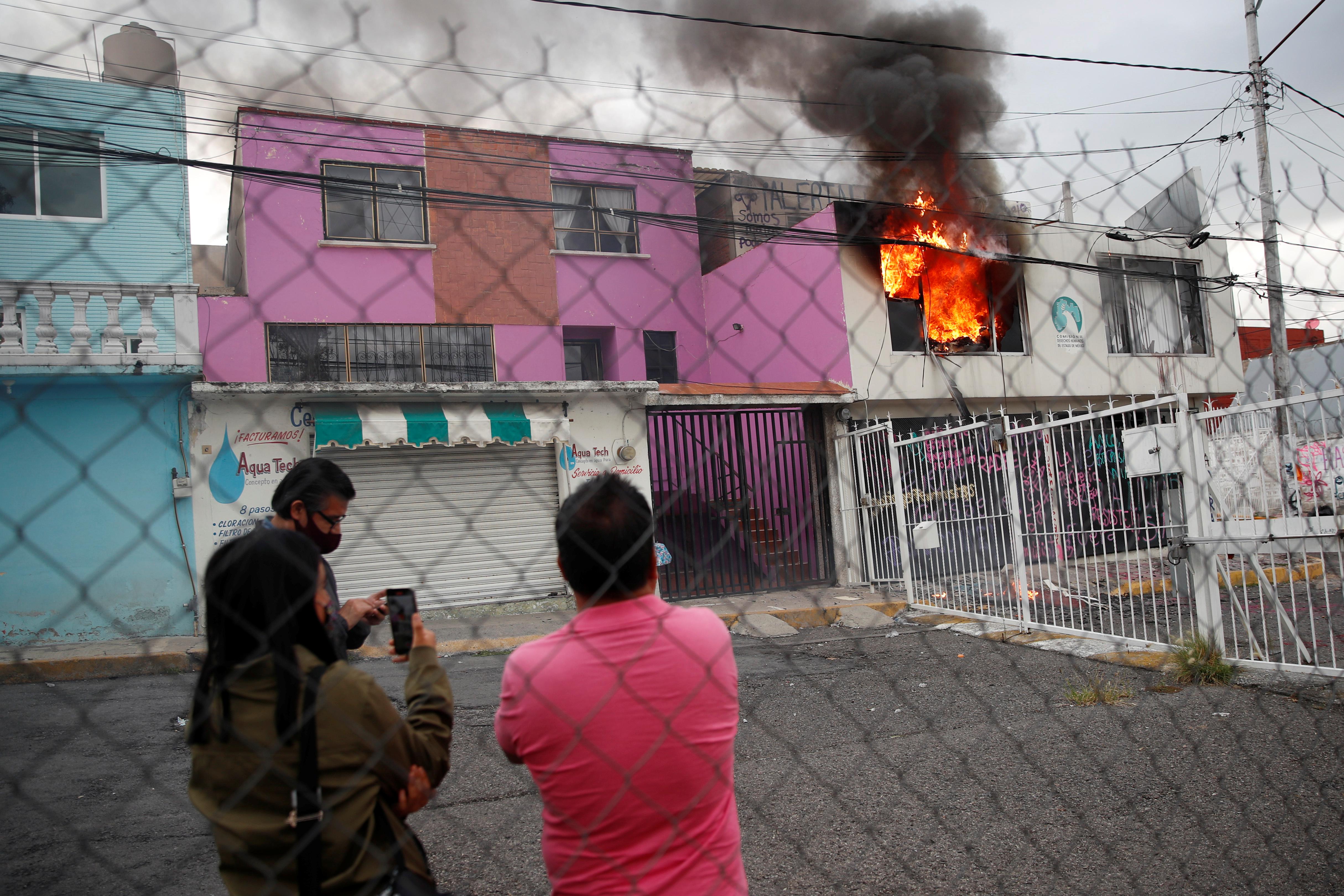 La gente observa un incendio que estalló luego de que miembros de un colectivo feminista destrozaran las instalaciones de la comisión de derechos humanos del estado de México, en apoyo a víctimas de violencia de género, en Ecatepec, Estado de México, México el 11 de septiembre de 2020.
