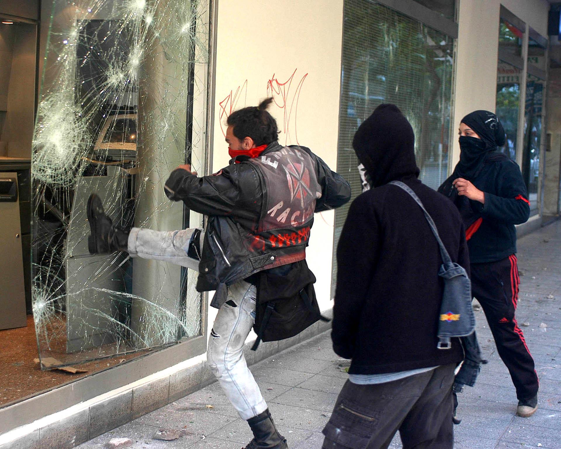 Un manifestante rompe una vidriera durante los incidentes que se produjeron en la avenida Colón