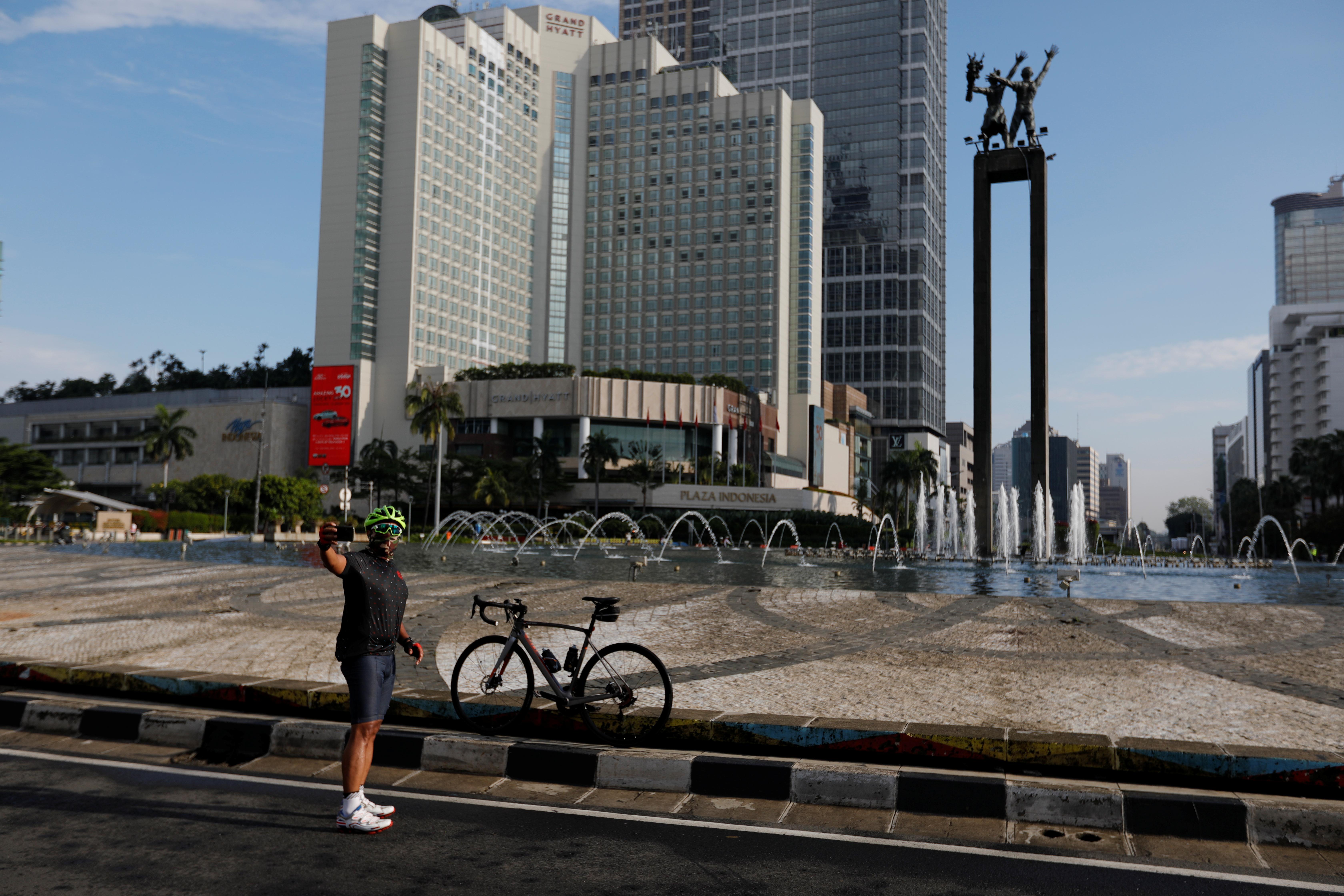 Una ciclista se toma una selfie frente a una fuente de aguas danzantes en Jakarta, Indonesia (REUTERS/Willy Kurniawan)