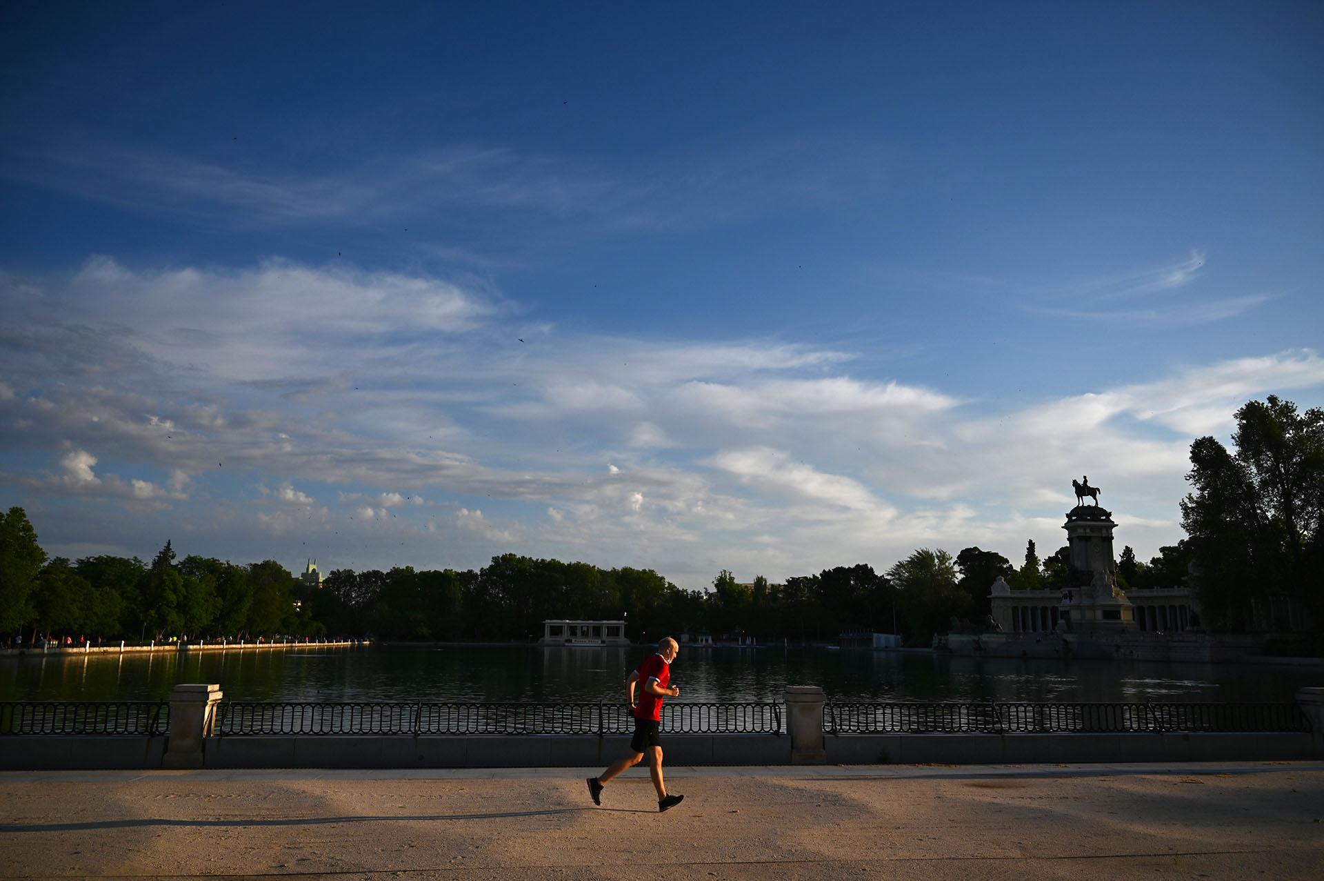 Un hombre corre en el parque de El Retiro. Los restaurantes pueden reabrir, limitando el número de clientes, y las salidas para los paseos o para practicar deporte ya no se limitan a ciertas horas del día. (Gabriel BOUYS / AFP)