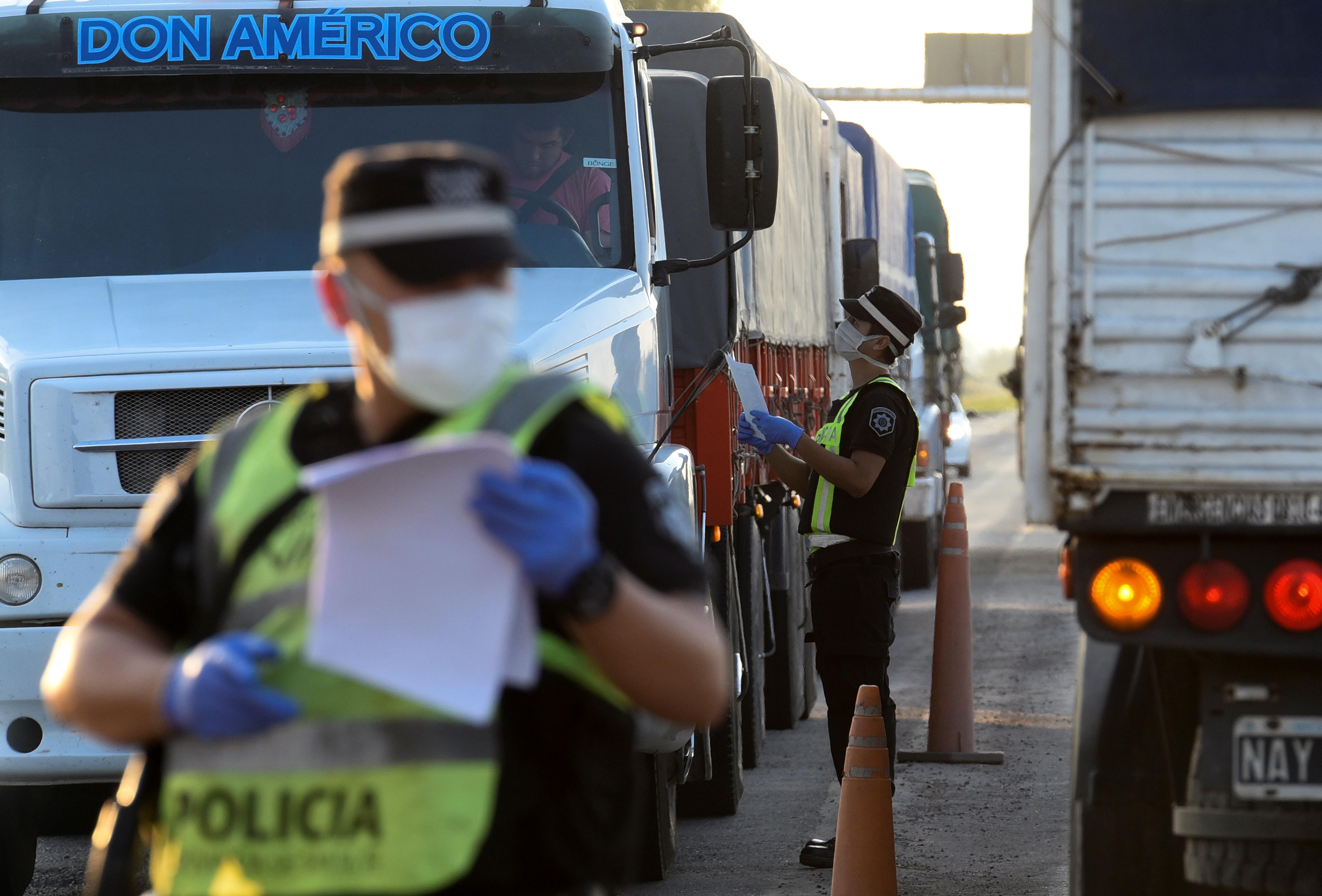 Un policía le pide el permiso para circular a un camionero, impedido de transportar sus granos debido al cierre de los cinco puertos cerealeros de la localidad de Timbúes, al sur de la provincia de Santa Fe. La medida fue tomada por Amaro González, el intendente local, hasta el 2 de abril. La imagen es en Iberlucea, un pueblo aledaño.