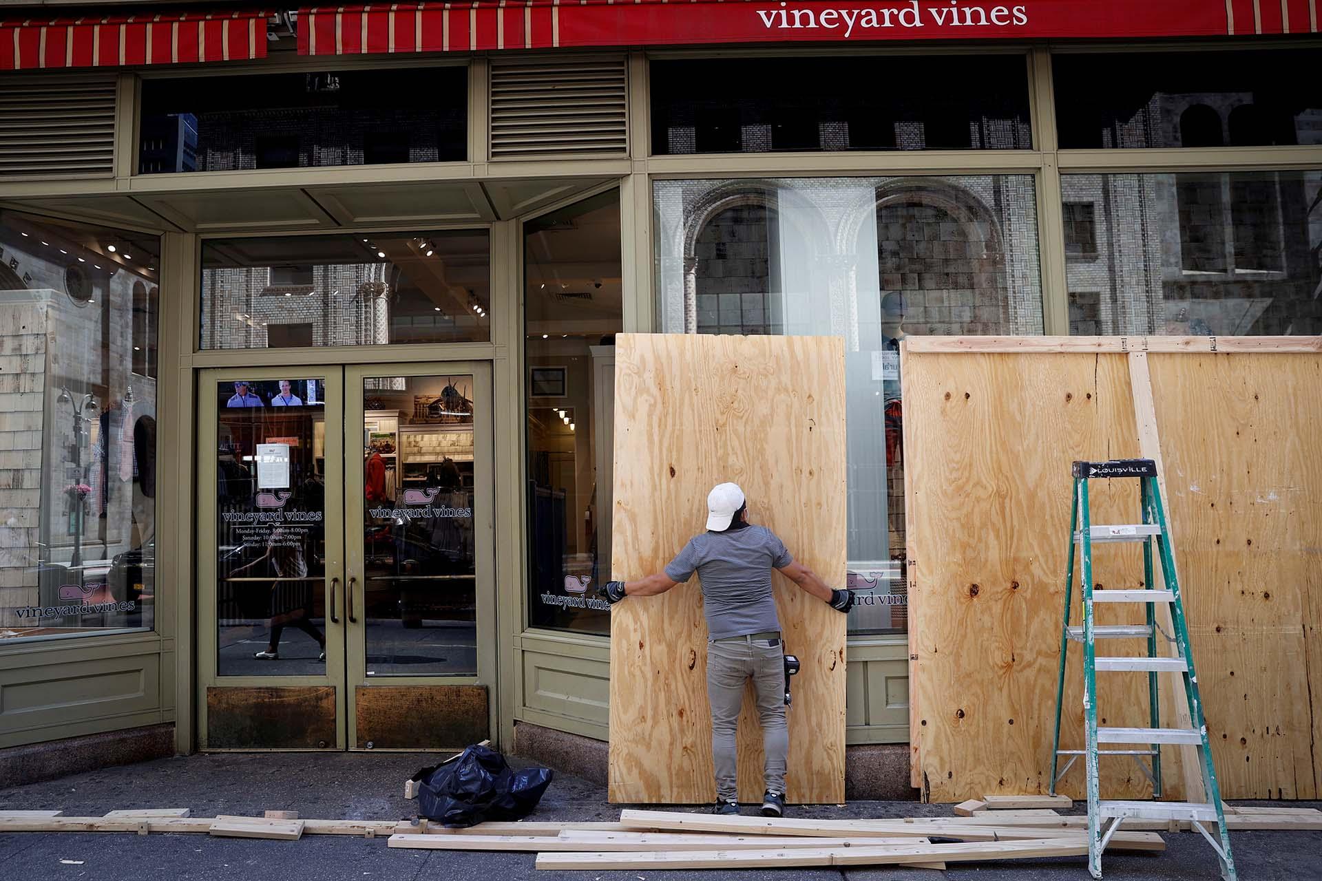 Un trabajador quita las maderas que protegieron las vitrinas de Vineyard Vines en Manhattan, durante las protestas contra el racismo de la última semana (REUTERS)