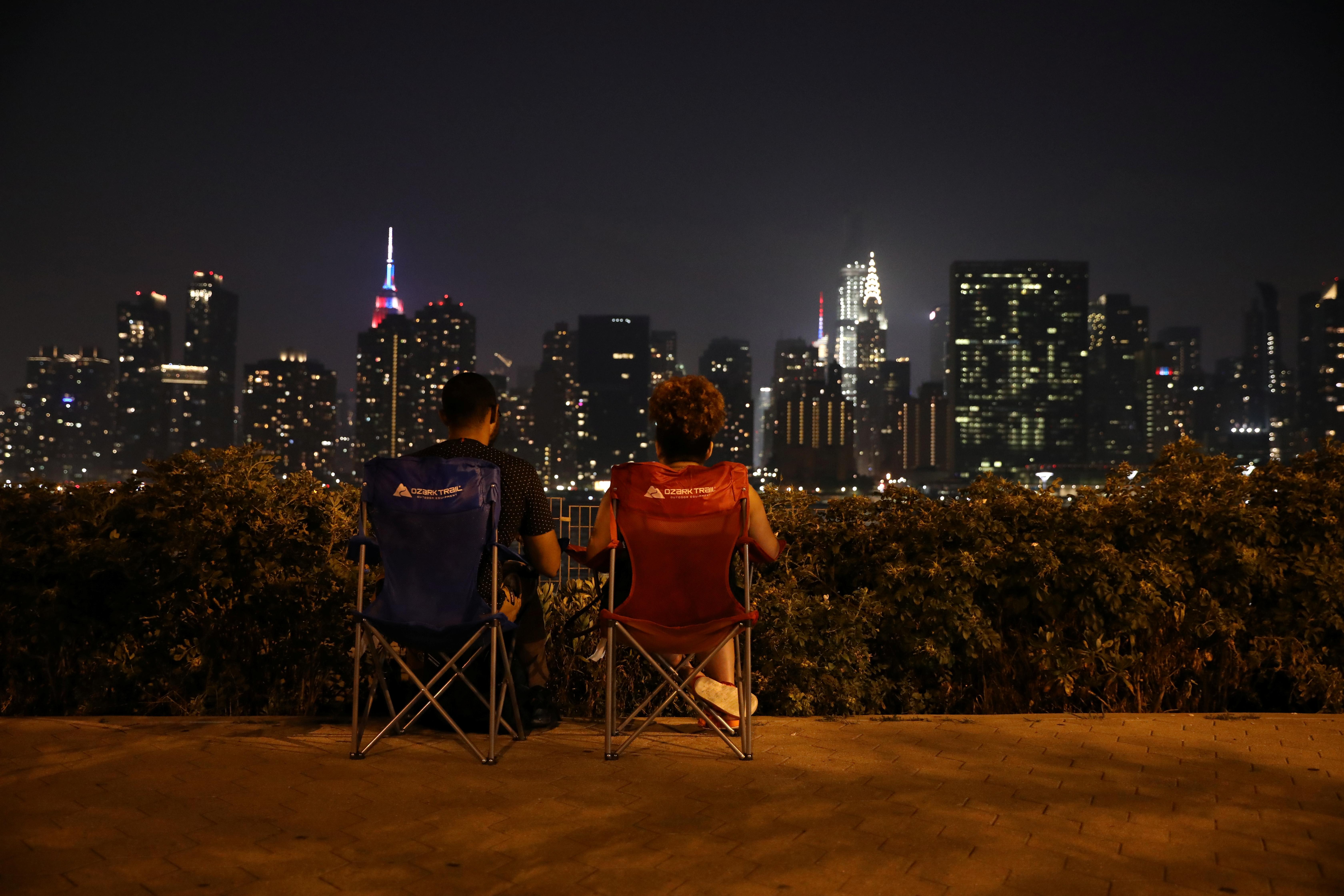 Una pareja mira sentados los fuegos artificiales