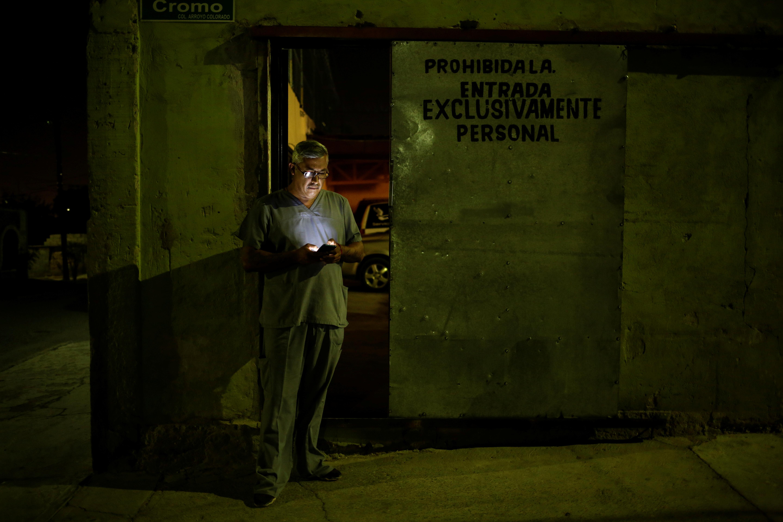 Un empleado de la funeraria Ríos revisa su teléfono fuera de la funeraria, mientras continúa el brote del coronavirus (COVID-19), en Ciudad Juárez, México, el 23 de octubre de 2020.