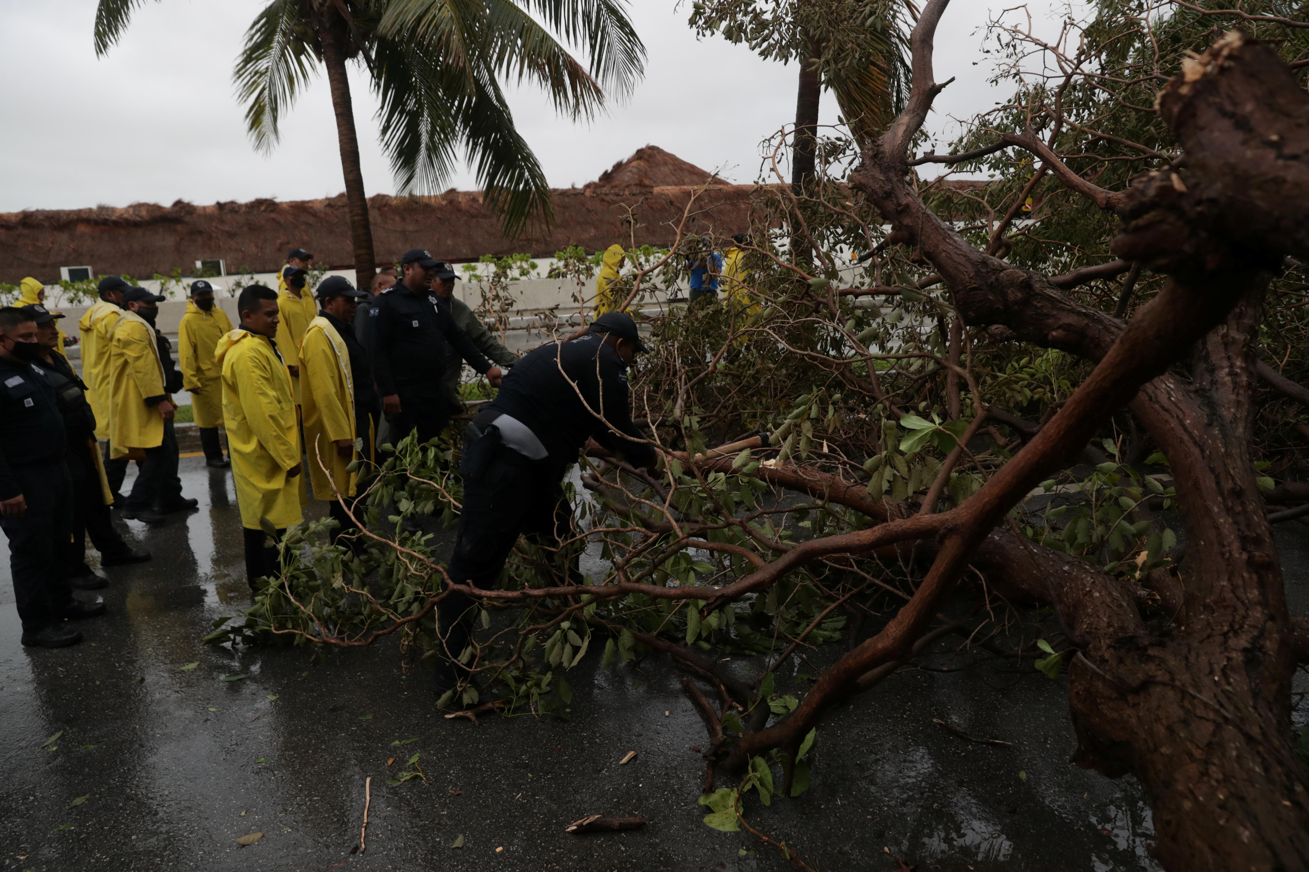 Agentes de policía retiran ramas de un árbol tras el paso del huracán Delta, en el estado de Quintana Roo, en Cancún, México, el 7 de octubre de 2020.