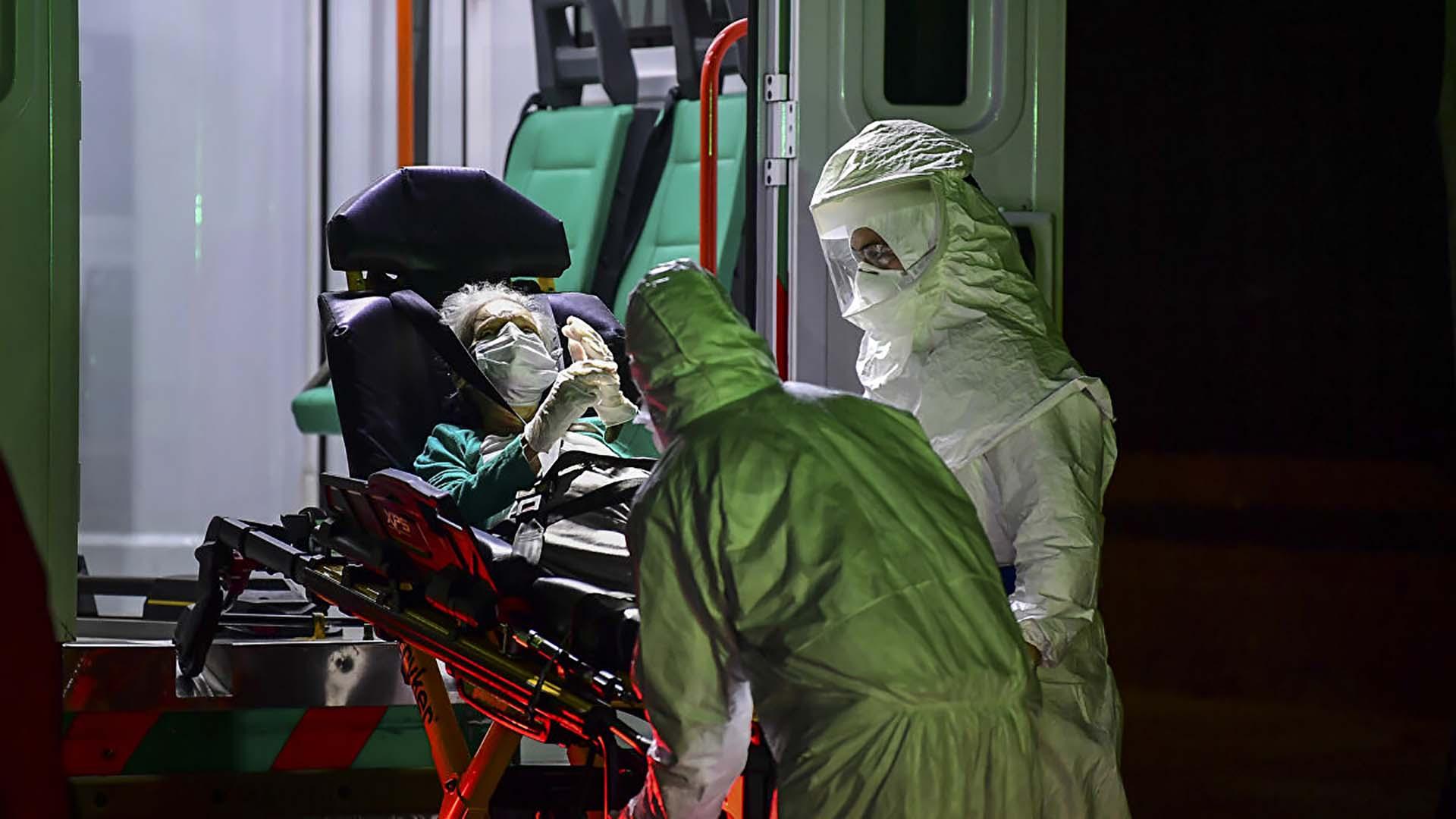 Un anciano con mascarilla y guantes, presuntamente infectado con COVID-19, es trasladado de un geriátrico a una ambulancia del SAME en el barrio Belgrano