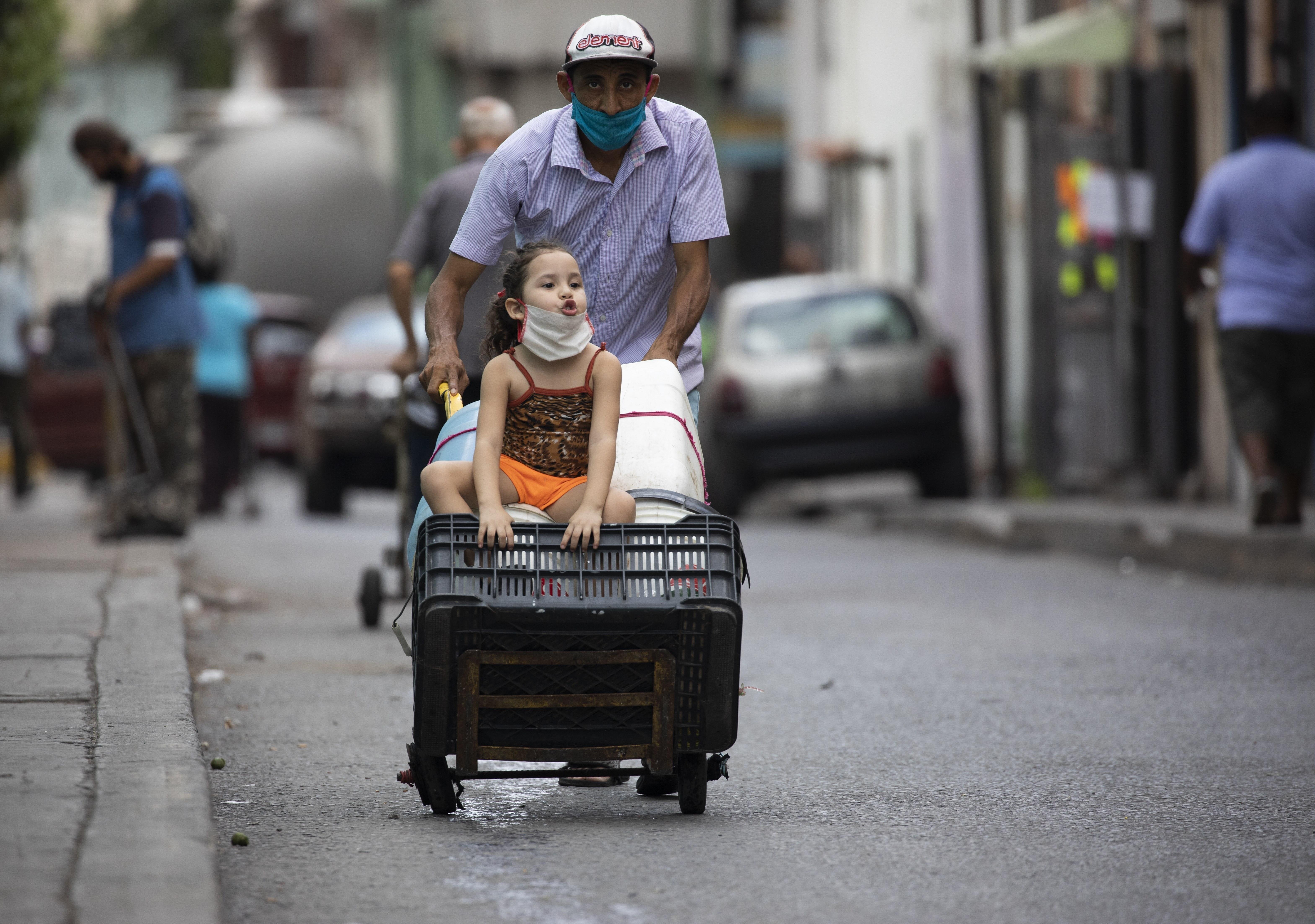 Un hombre, con mascarilla para protegerse del coronavirus, empuja un carrito lleno de recipientes de agua vacíos mientras va, acompañado de una niña, en busca de agua, en Caracas, Venezuela, el 20 de junio de 2020. Sin agua corriente en sus casas, los residentes no tienen más opción que salir a buscarla, violando la cuarentena decretada en todo el país para combatir la pandemia. (AP Foto/Ariana Cubillos)