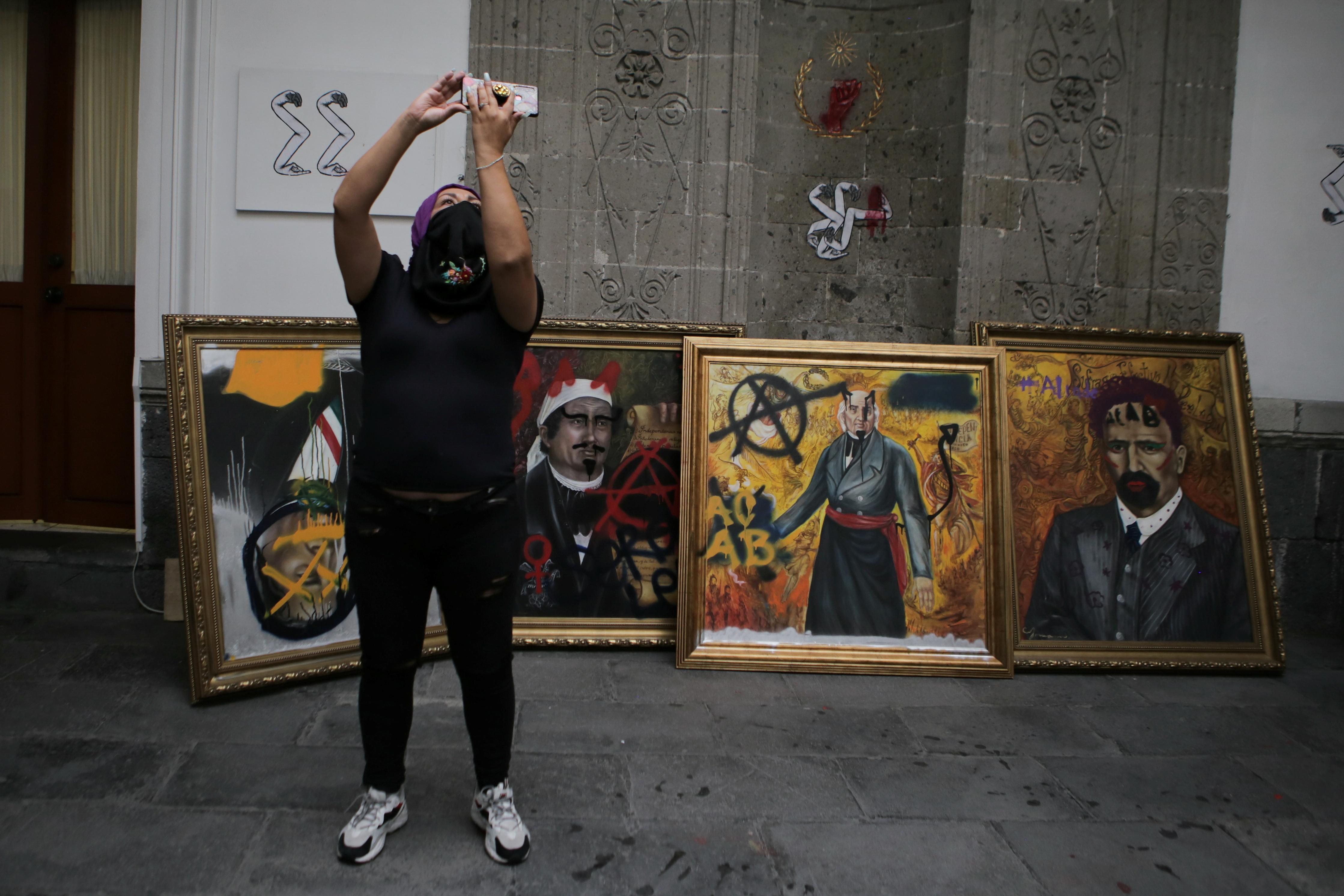 Una integrante de un colectivo feminista se toma una selfie junto a retratos vandalizados de líderes mexicanos dentro de las instalaciones del edificio de la Comisión Nacional de Derechos Humanos, en apoyo a las víctimas de violencia de género, en la Ciudad de México, México, 10 de septiembre de 2020. Fotografía tomada el 10 de septiembre de 2020.