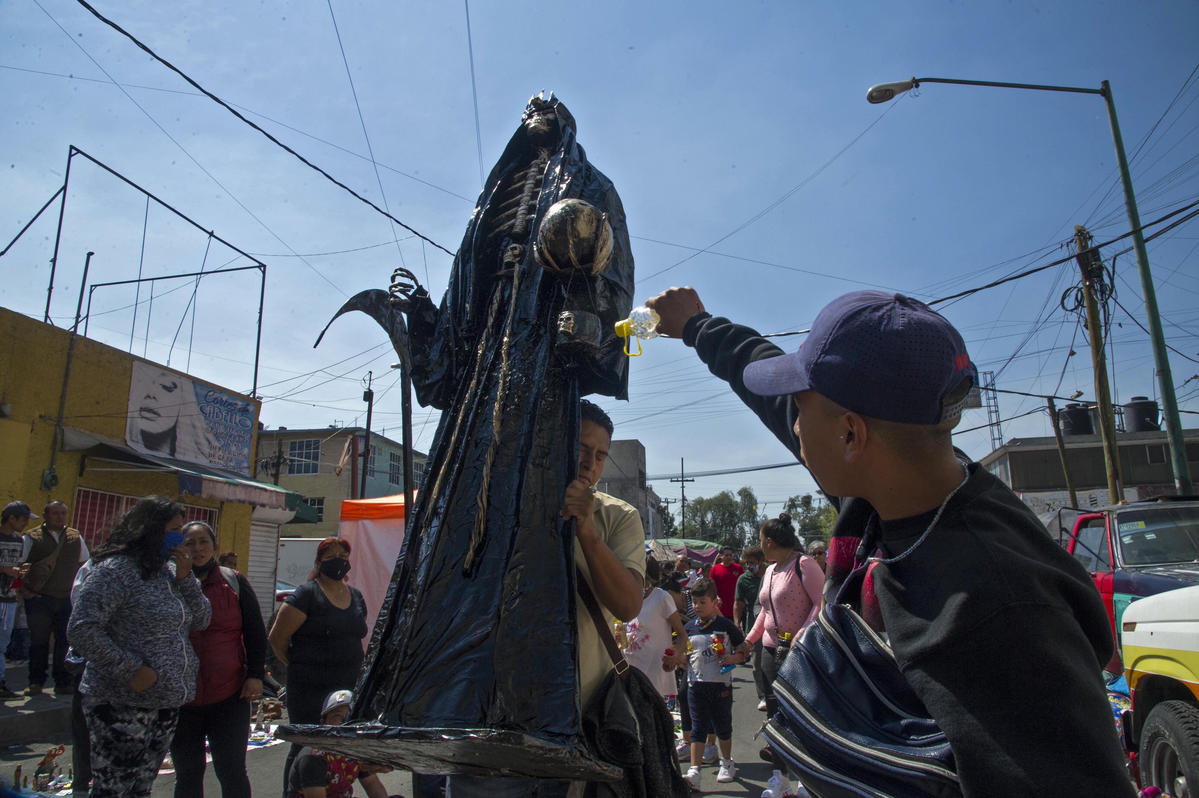Un hombre rocía alcohol etílico sobre una figura de la Santa Muerte como ritual de limpieza cerca de su santuario en la calle Alfarería, en el barrio de Tepito, de la Ciudad de México, el 1 de octubre de 2020