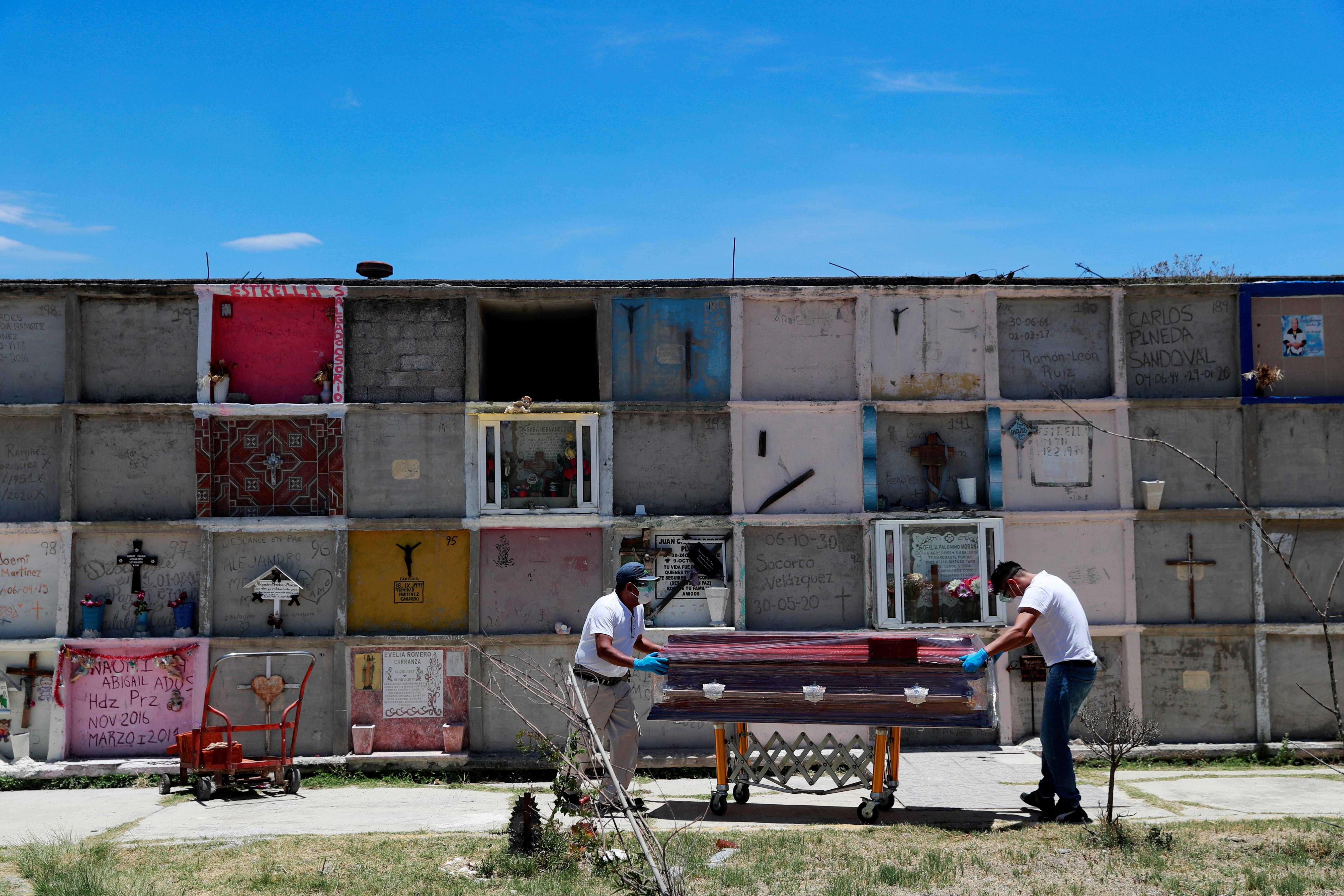Los trabajadores funerarios mueven el ataúd de una mujer, que murió de la enfermedad del coronavirus (COVID-19), en el cementerio municipal de Nezahualcóyotl, Estado de México, México, 12 de junio de 2020. Foto: Reuters.