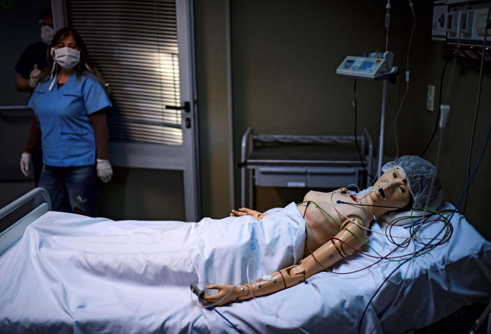 La doctora Norma Raúl observa un robot con el que practica la asistencia médica a pacientes con COVID-19, en el Centro de Capacitación en Simulación Clínica del hospital El Cruce, en Florencio Varela, provincia de Buenos Aires