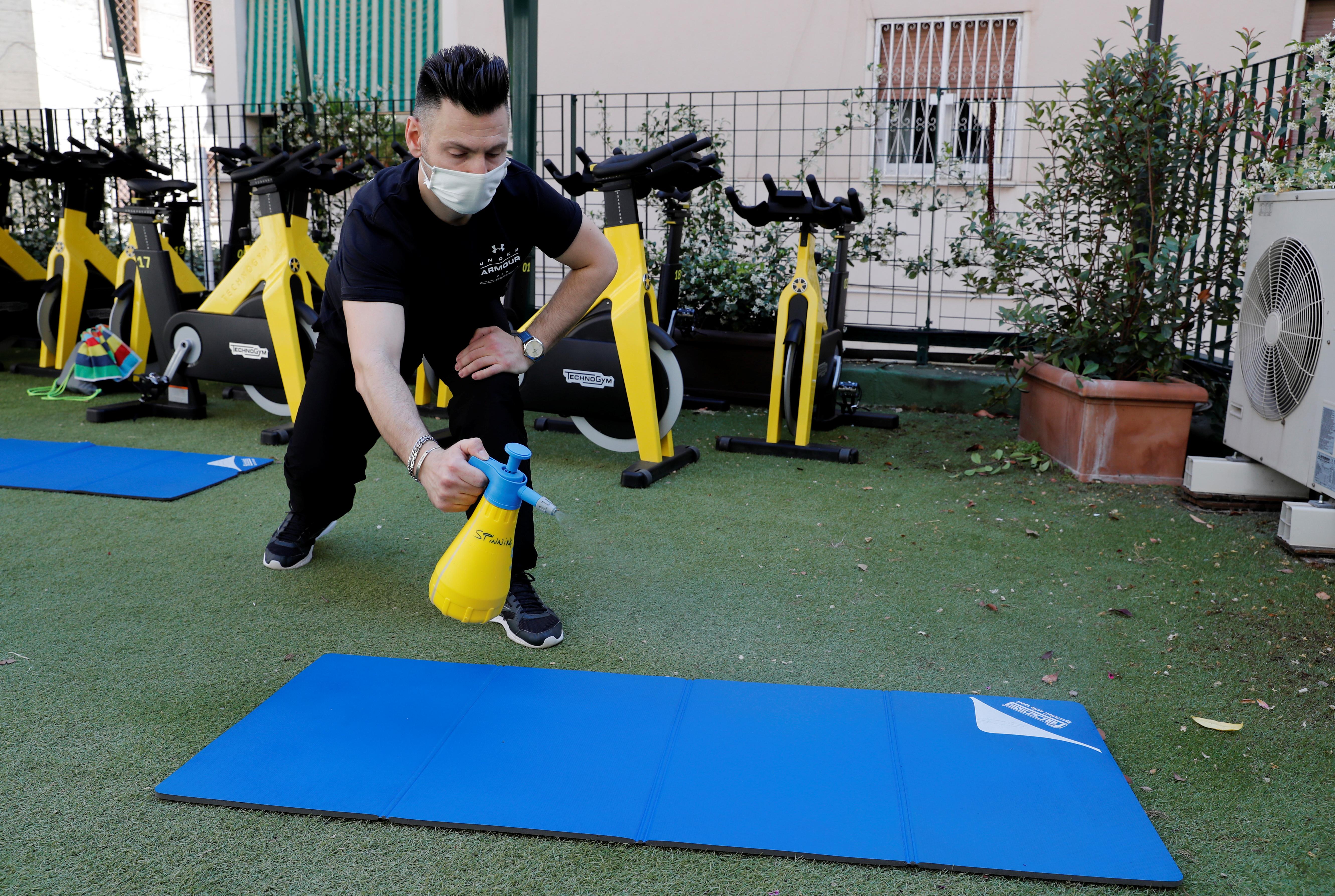 Tanto en los gimnasios como en las piscinas se podrá tomar la temperatura de la gente, aunque no es una obligación, y prohibir la entrada a partir de 37,5°. En la foto, un personal trainer en un gimnasio en Roma (REUTERS/Remo Casilli)