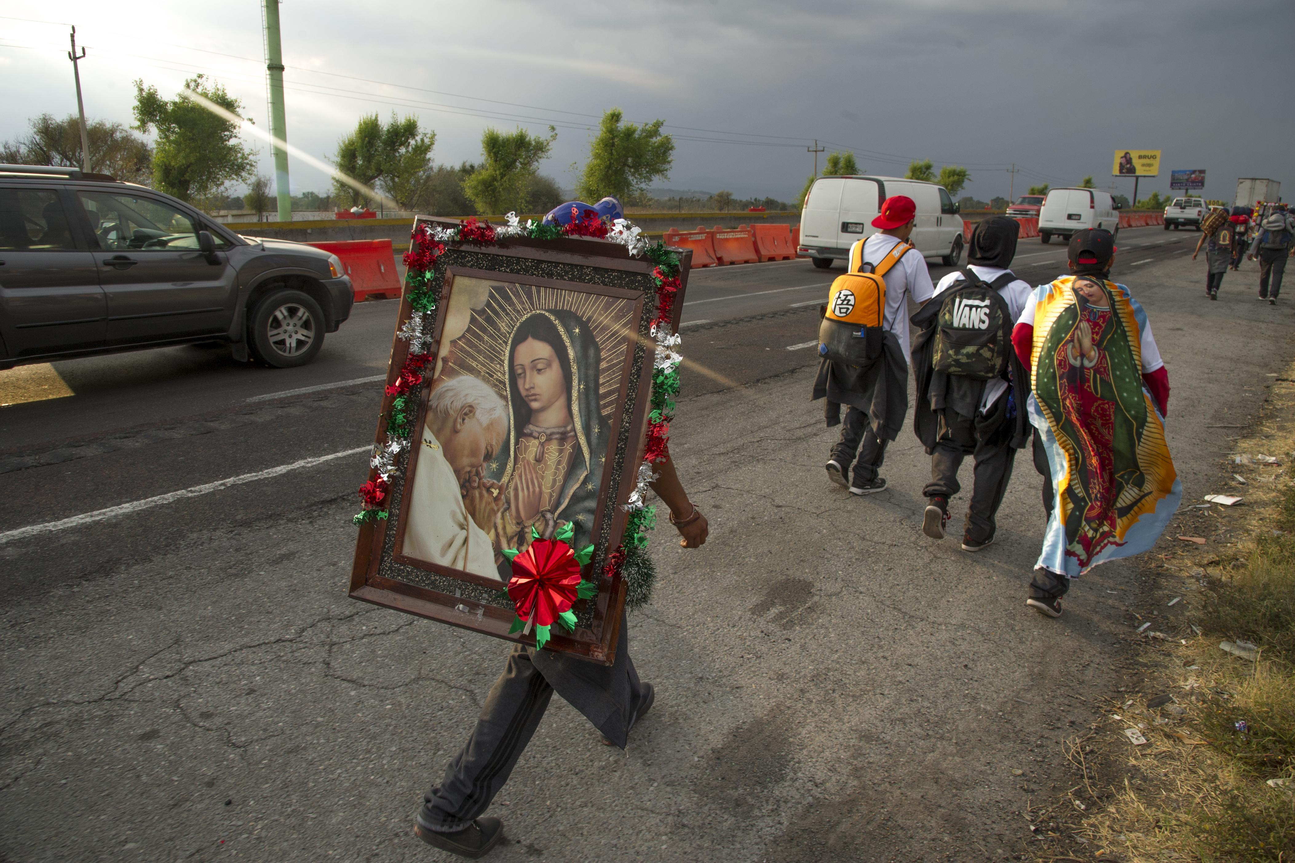 Los peregrinos llevan imágenes de la Virgen de Guadalupe mientras caminan por una carretera federal en Puebla, México, de camino a la Basílica de Guadalupe en la Ciudad de México, el 7 de diciembre de 2020.