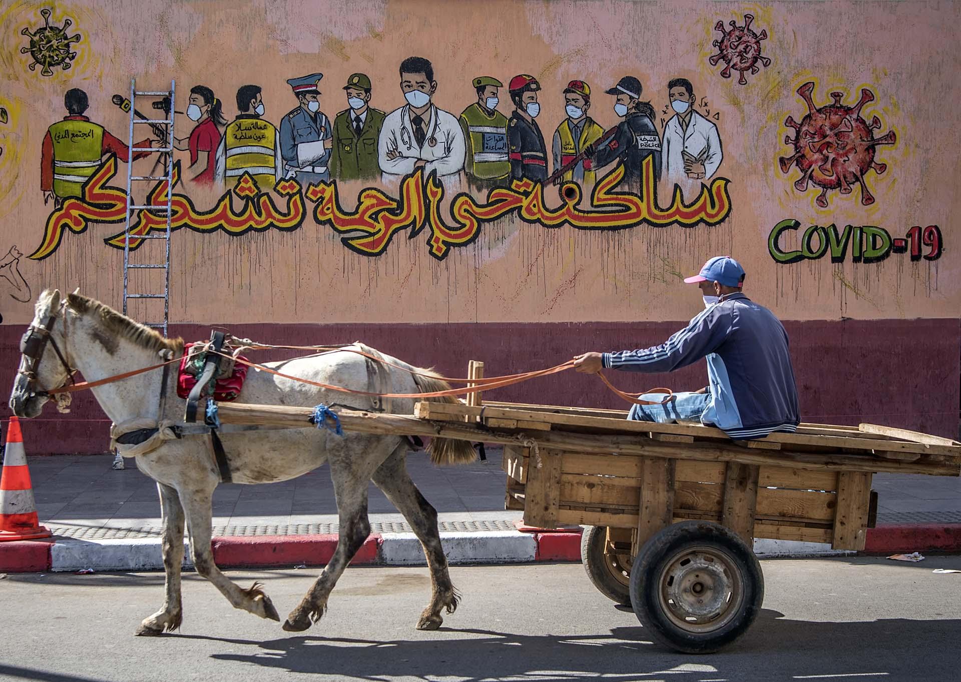 Un hombre pasa con su carro tirado por un caballo frente a un mural pintado en una pared de Sale, cerca de la capital de Marruecos.