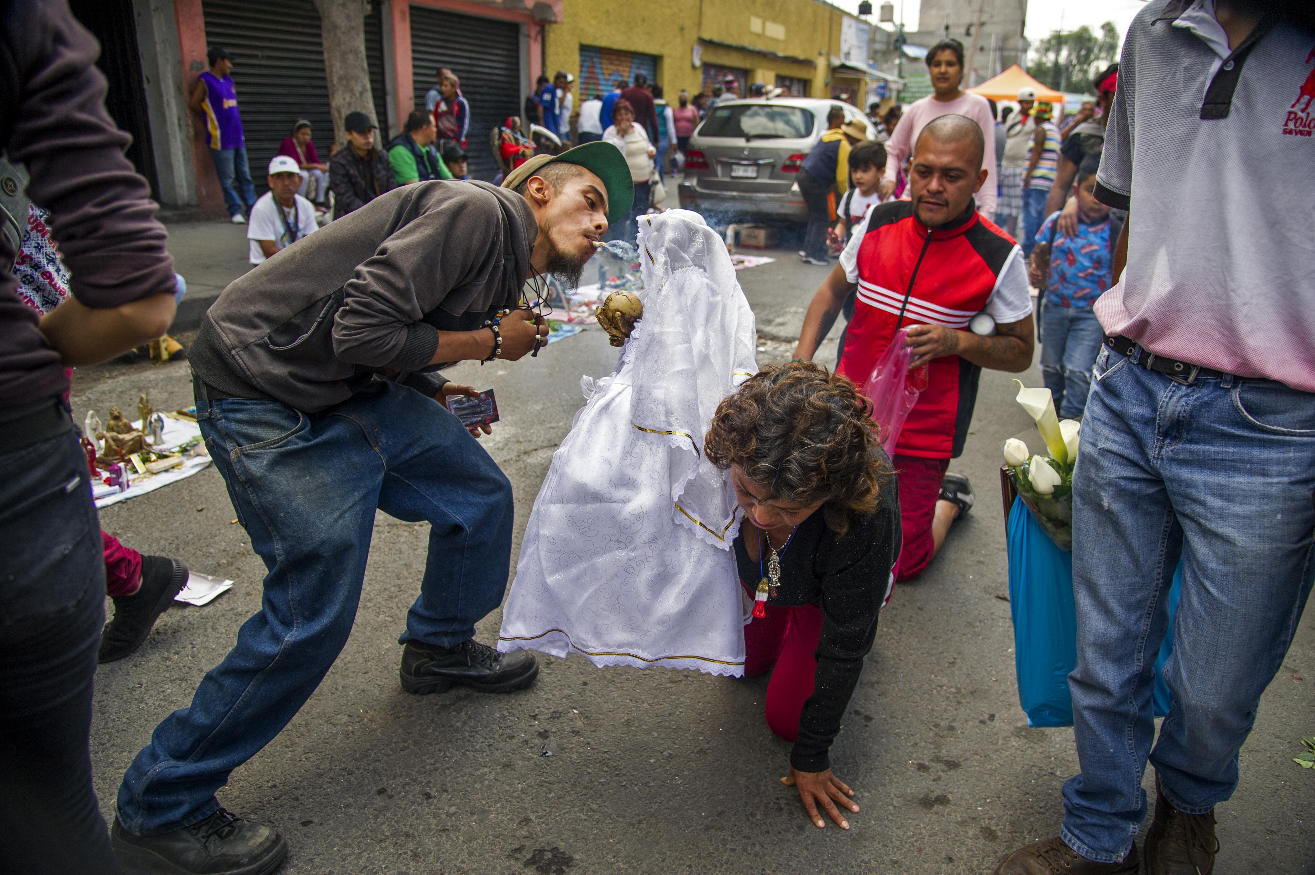 Una mujer camina de rodillas portando una figura de la Santa Muerte frente a su santuario en la calle Alfarería, en el barrio de Tepito, de la Ciudad de México, el 1 de octubre de 2020