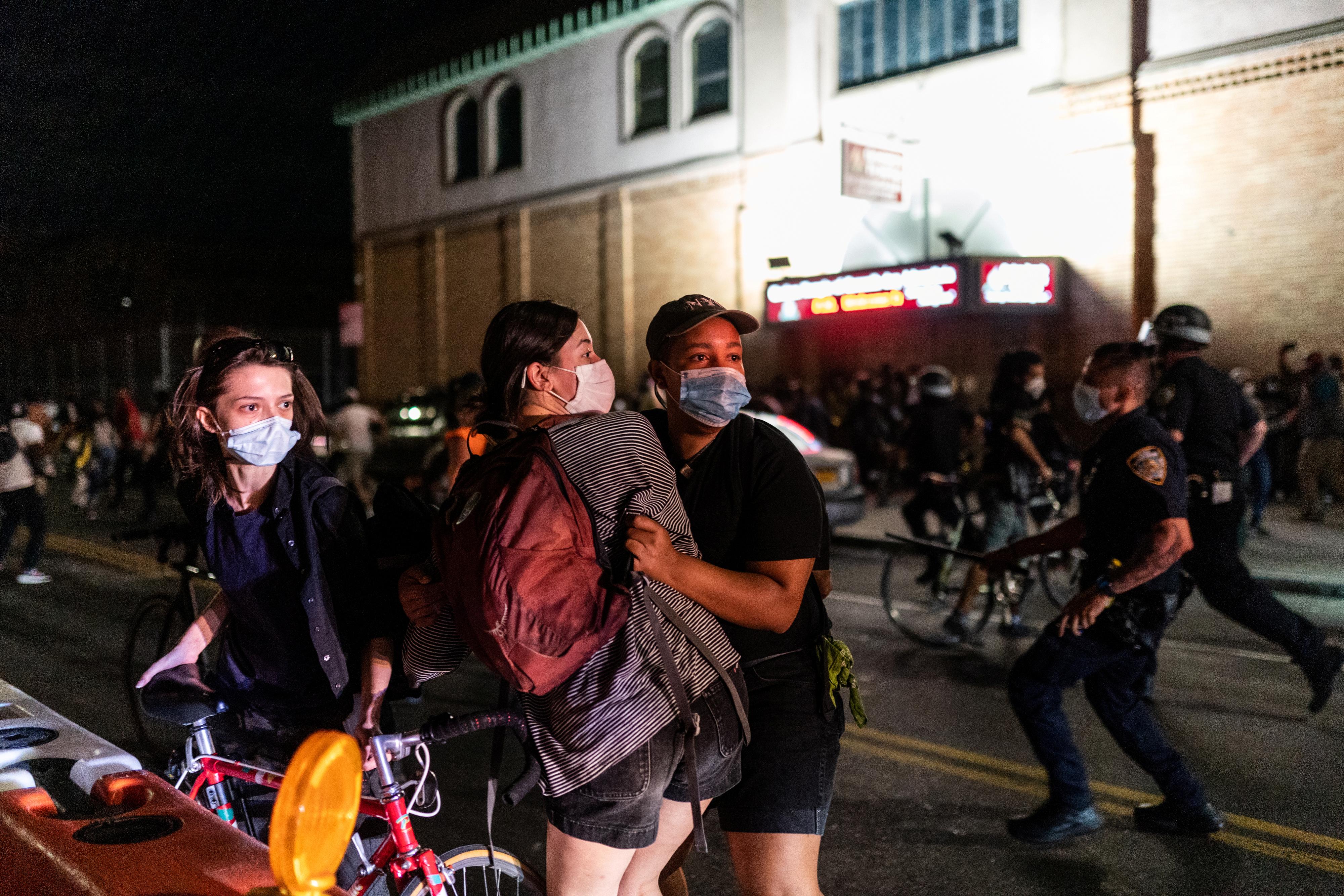 Mujeres se resguardan ante el avance de la policía en Brooklyn