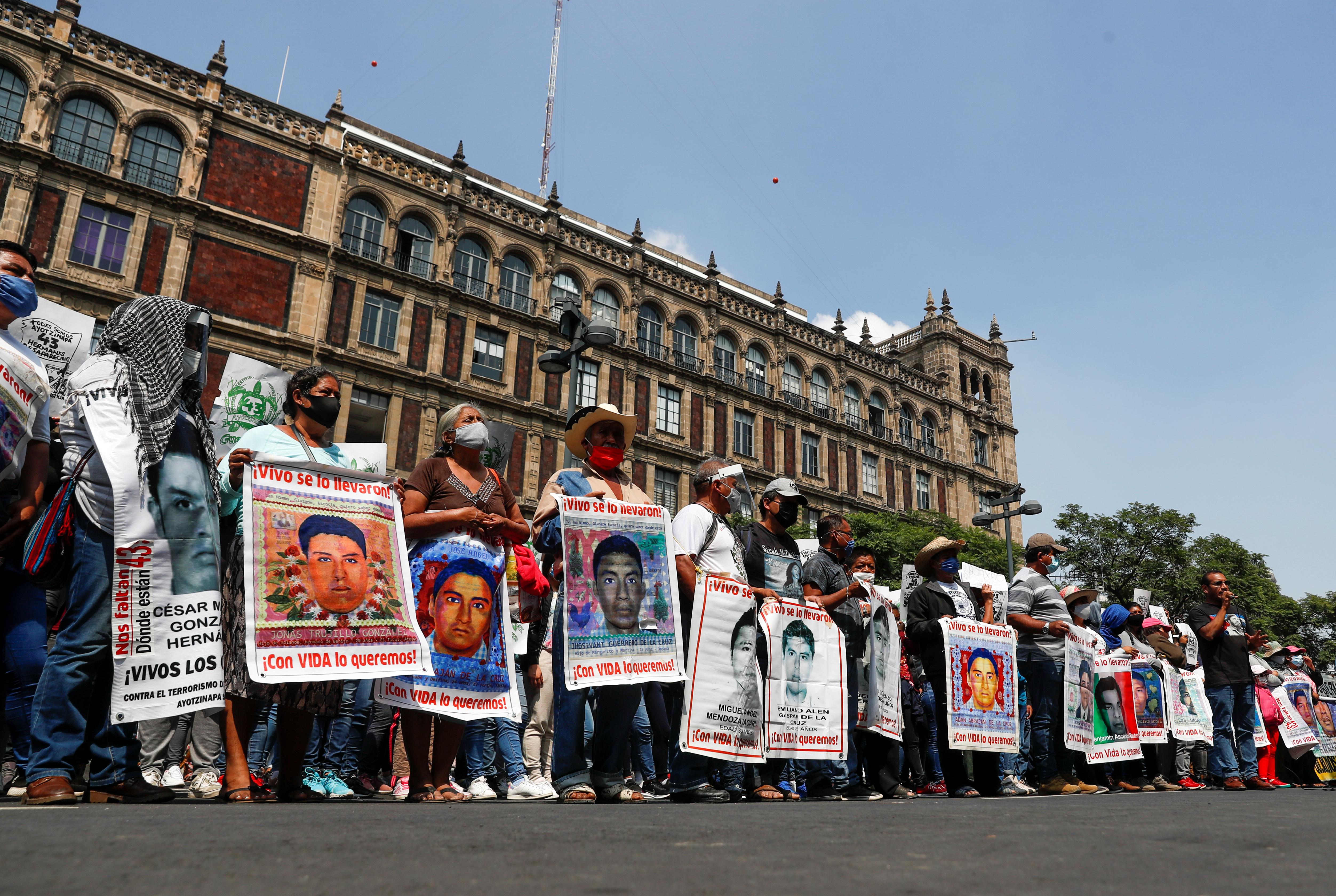 Familiares de estudiantes desaparecidos sostienen carteles con sus imágenes durante una protesta frente a la Corte Suprema de Justicia, antes del sexto aniversario de la desaparición de 43 estudiantes de la Escuela Normal Rural de Ayotzinapa, en la Ciudad de México, México 23 de septiembre de 2020.