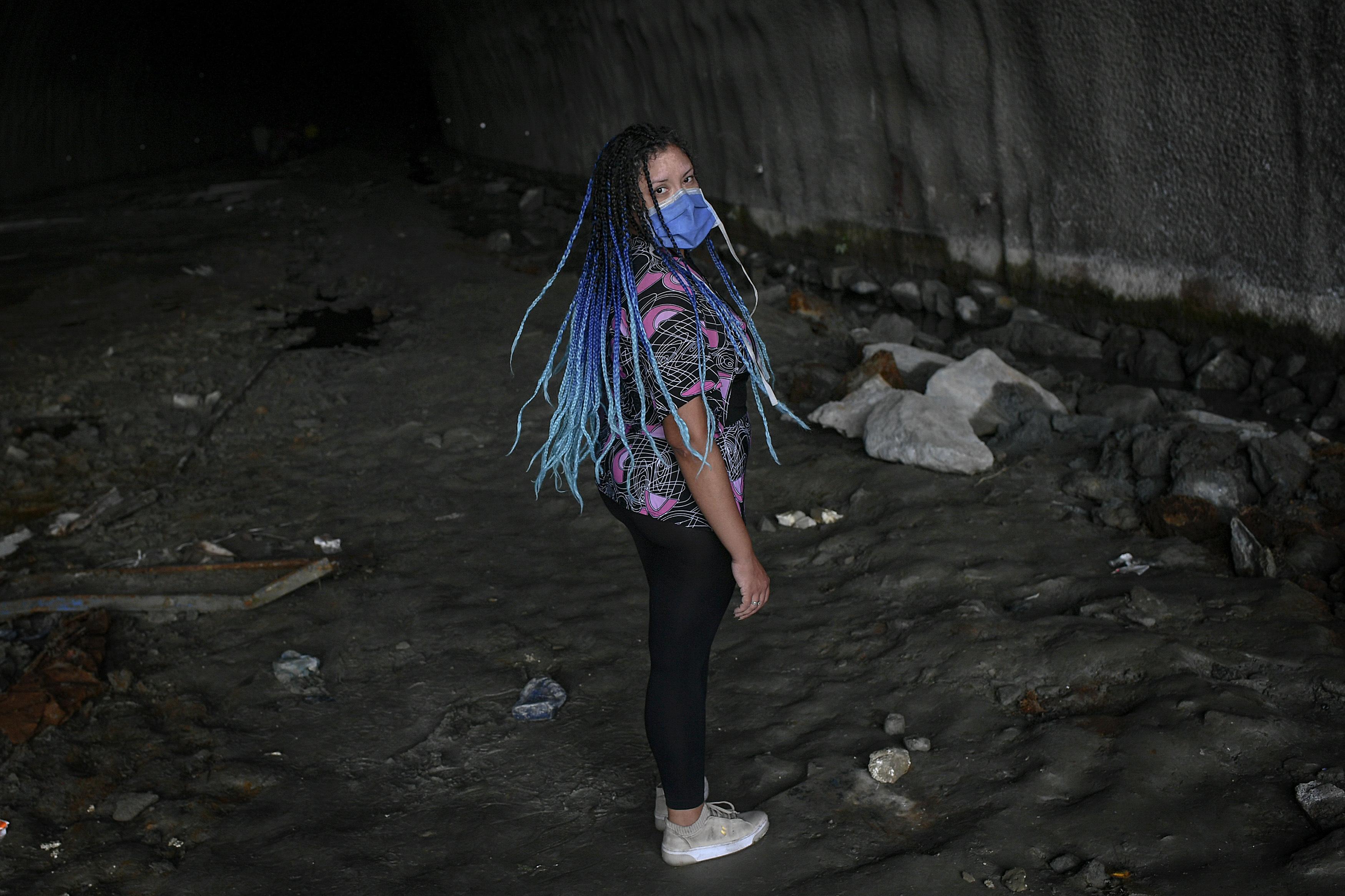 Una mujer con mascarilla se gira tras ser llamada por un amigo, en el túnel de la autopista Baralt en Caracas, Venezuela, el 7 de junio de 2020. Sin agua potable distribuida por el gobierno, los vecinos del vecindario de Esperanza se han organizado para buscar su propio suministro, aprovechando el agua almacenada en el interior de un túnel inacabado. (AP Foto/Matías Delacroix)
