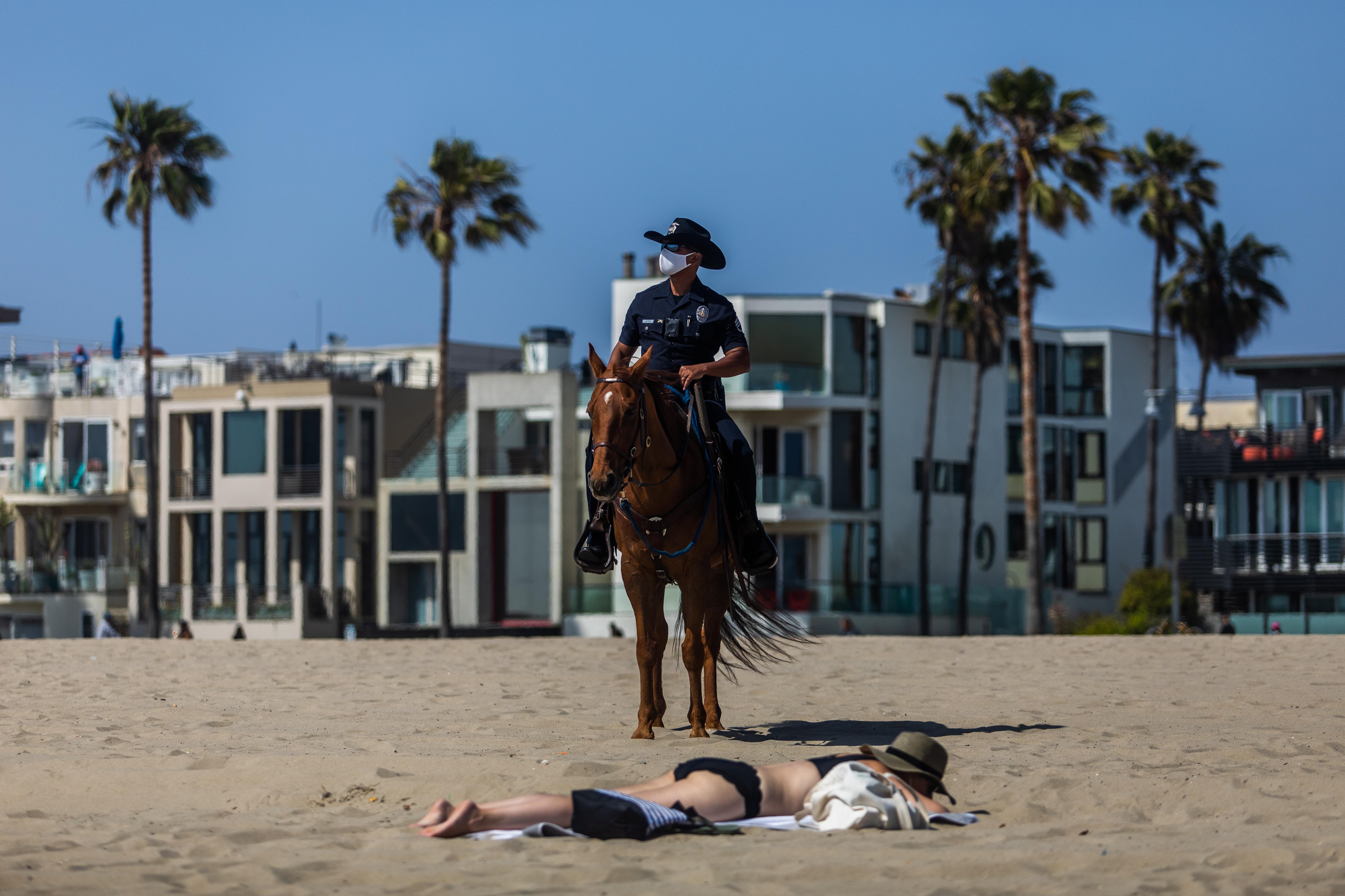 Un policía con mascarilla patrulla mientras una mujer se asolea en Venice Beach, California