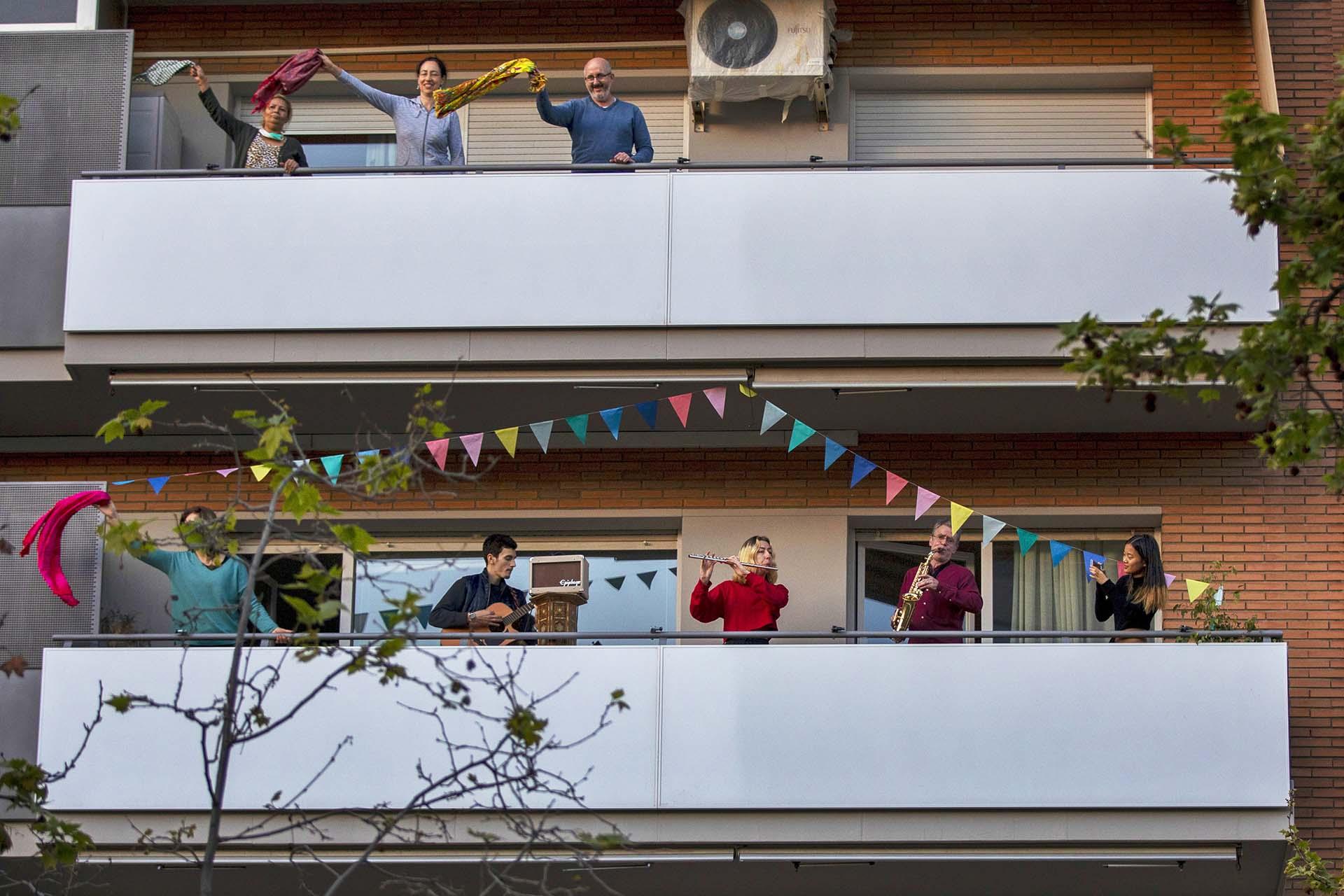 Vecinos hacen música mientras otro grupo baila en sus balcones en apoyo al personal médico en Barcelona, España (AP Photo/Emilio Morenatti, File)