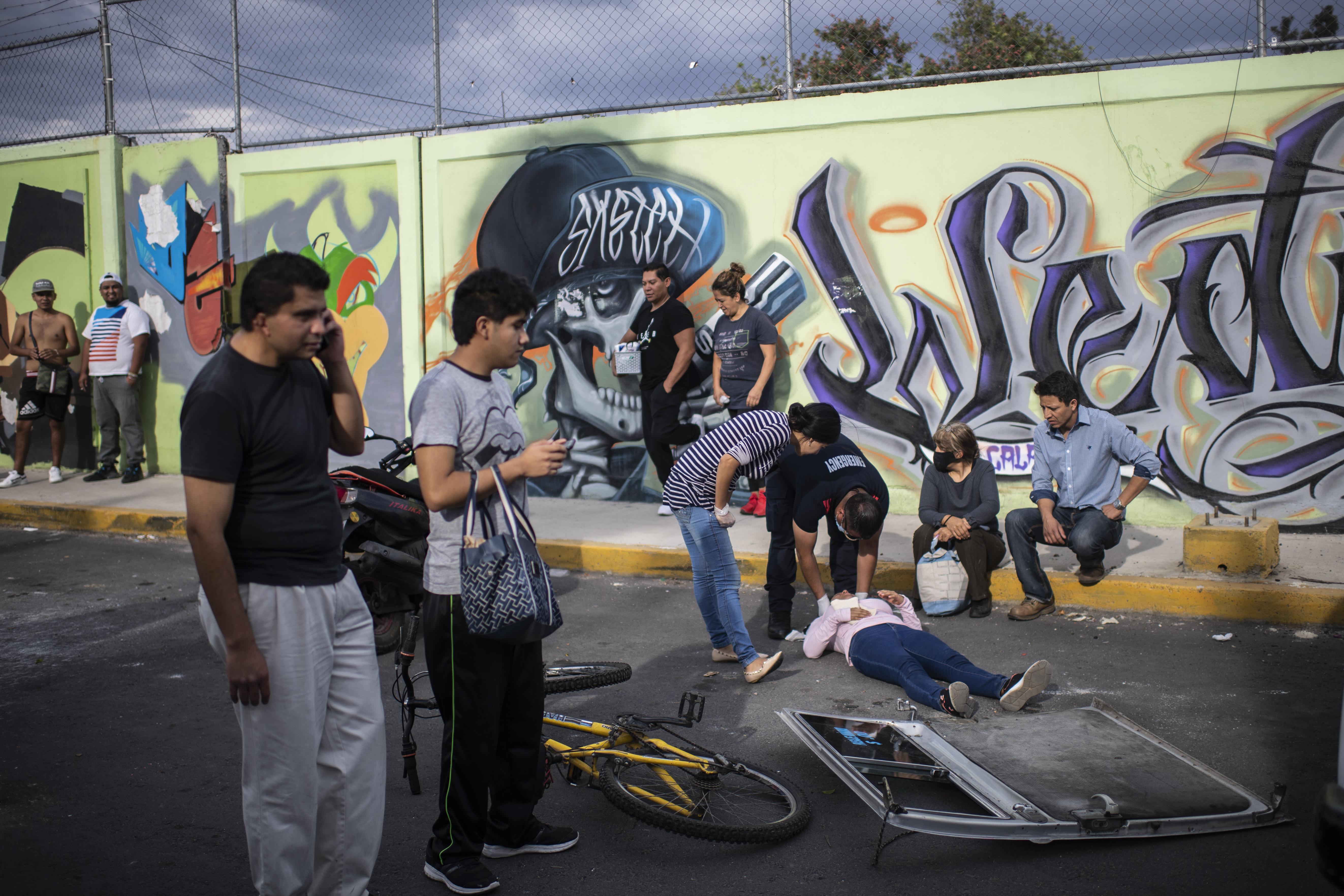 El paramédico Sergio Villafan revisa a una mujer involucrada en un accidente en Ciudad Nezahualcóyotl, Estado de México, México, el 18 de junio de 2020 durante la nueva pandemia de coronavirus de COVID-19. (Foto por Pedro PARDO / AFP)