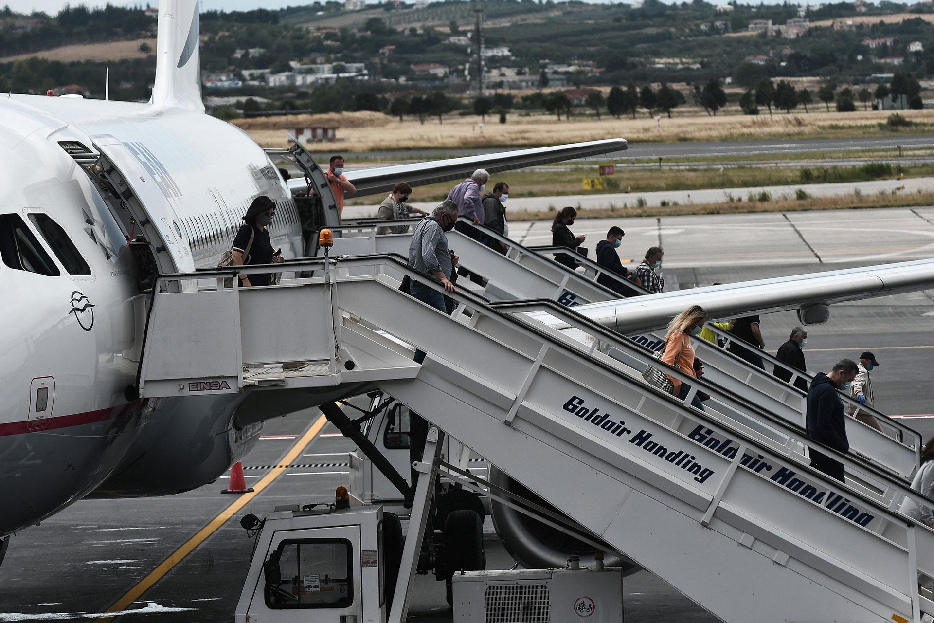Pasajeros de un vuelo procedente de Alemania desembarca en el aeropuerto griego de Tesalonika.