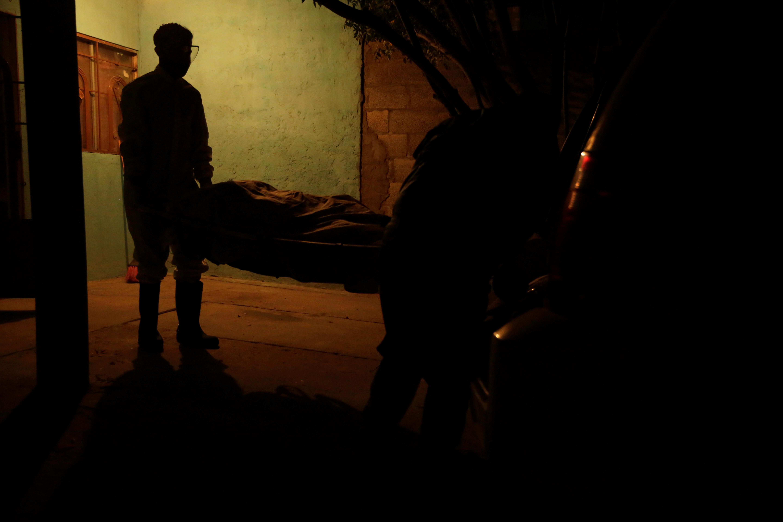 Empleados de la funeraria Ríos llevan el cuerpo de una mujer, que murió por coronavirus (COVID-19), fuera de su casa en Ciudad Juárez, México, 22 de octubre de 2020.
