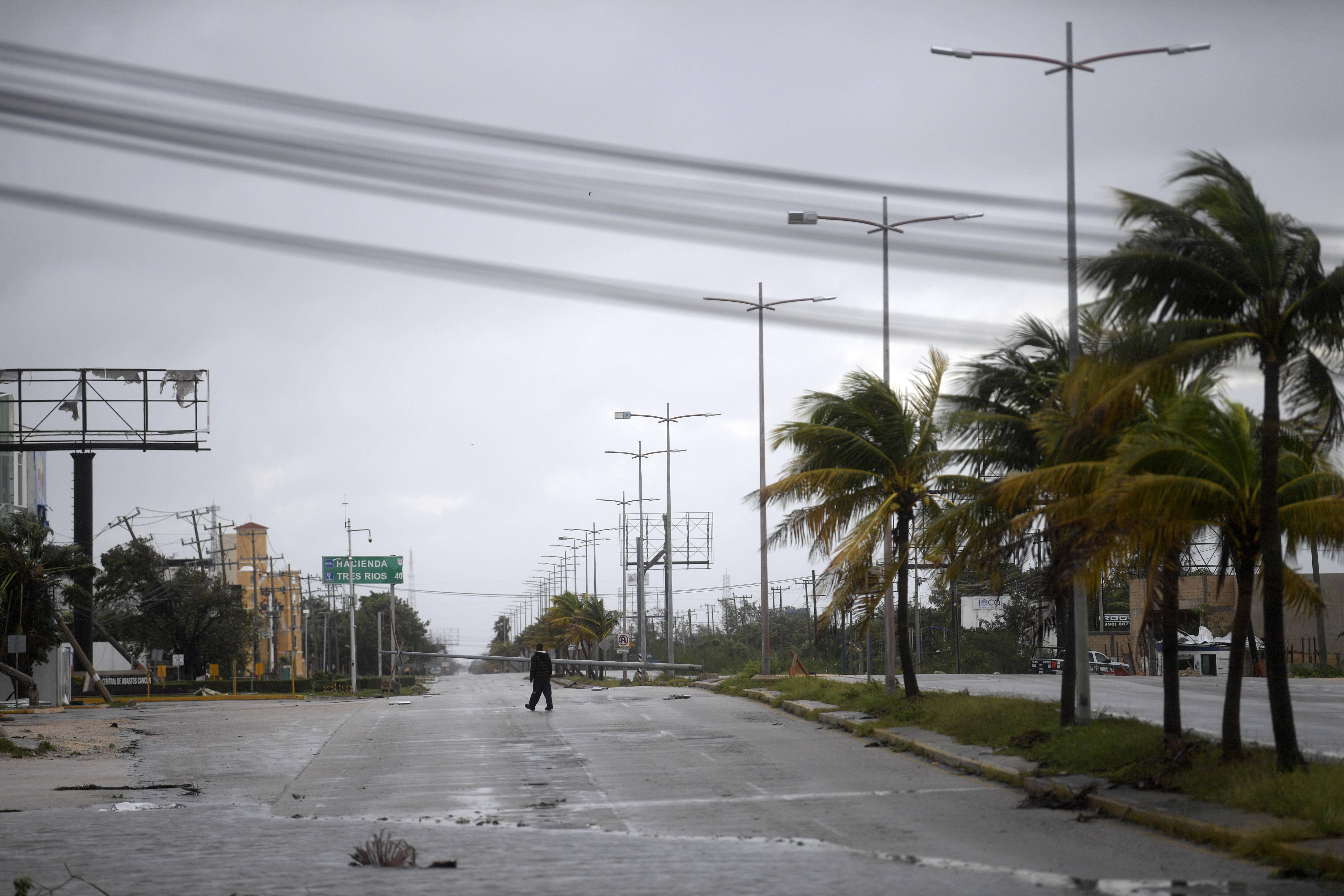Un hombre camina por una carretera dañada tras el paso del huracán Delta en Cancún, estado de Quintana Roo, México, el 7 de octubre de 2020.