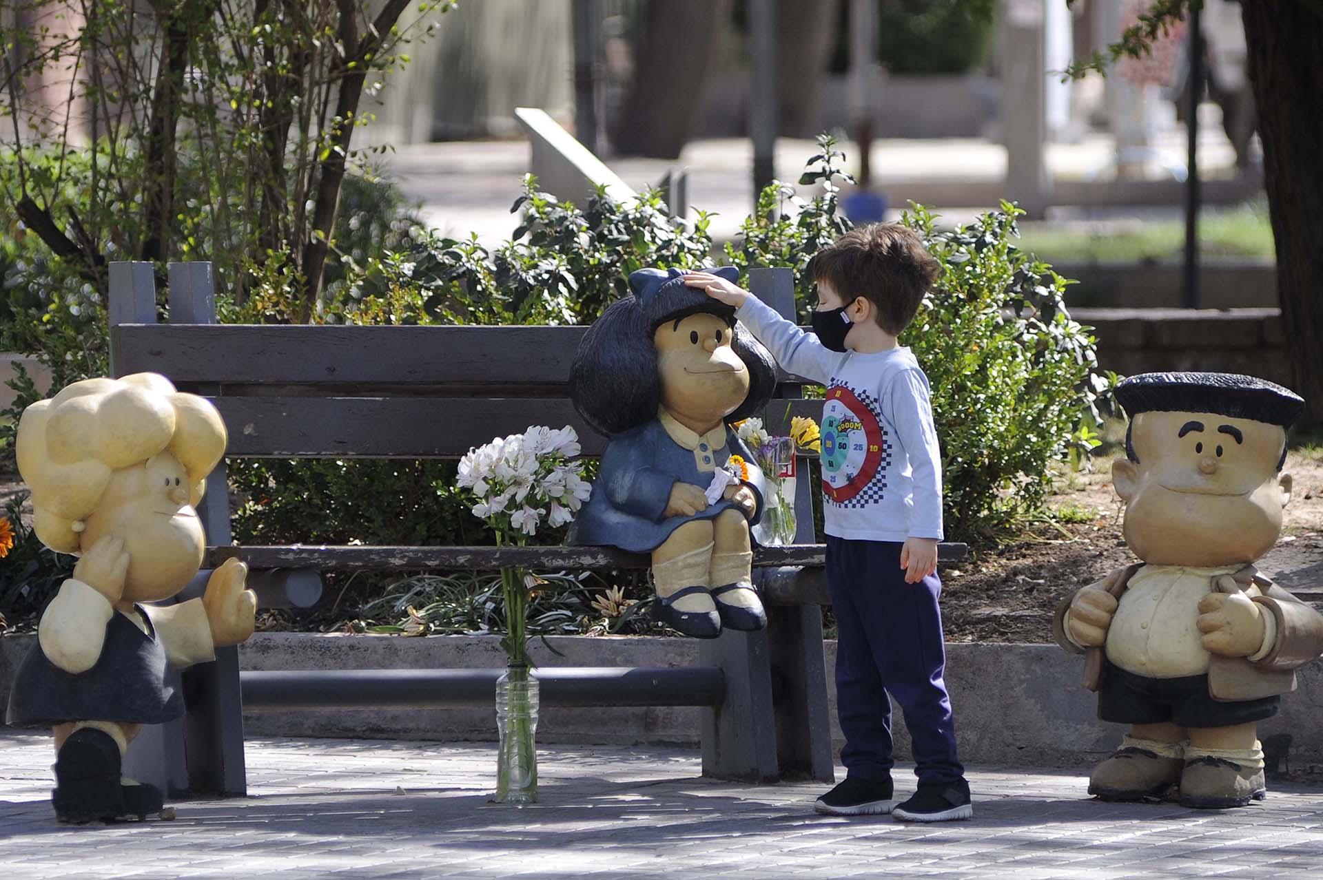 Un niño toca una estatua de Mafalda para enviarle un mimo a su creador, el célebre dibujante argentino Joaquín Salvador Lavado, conocido como Quino. El 30 de septiembre de 2020, a sus 88 años, falleció en Mendoza