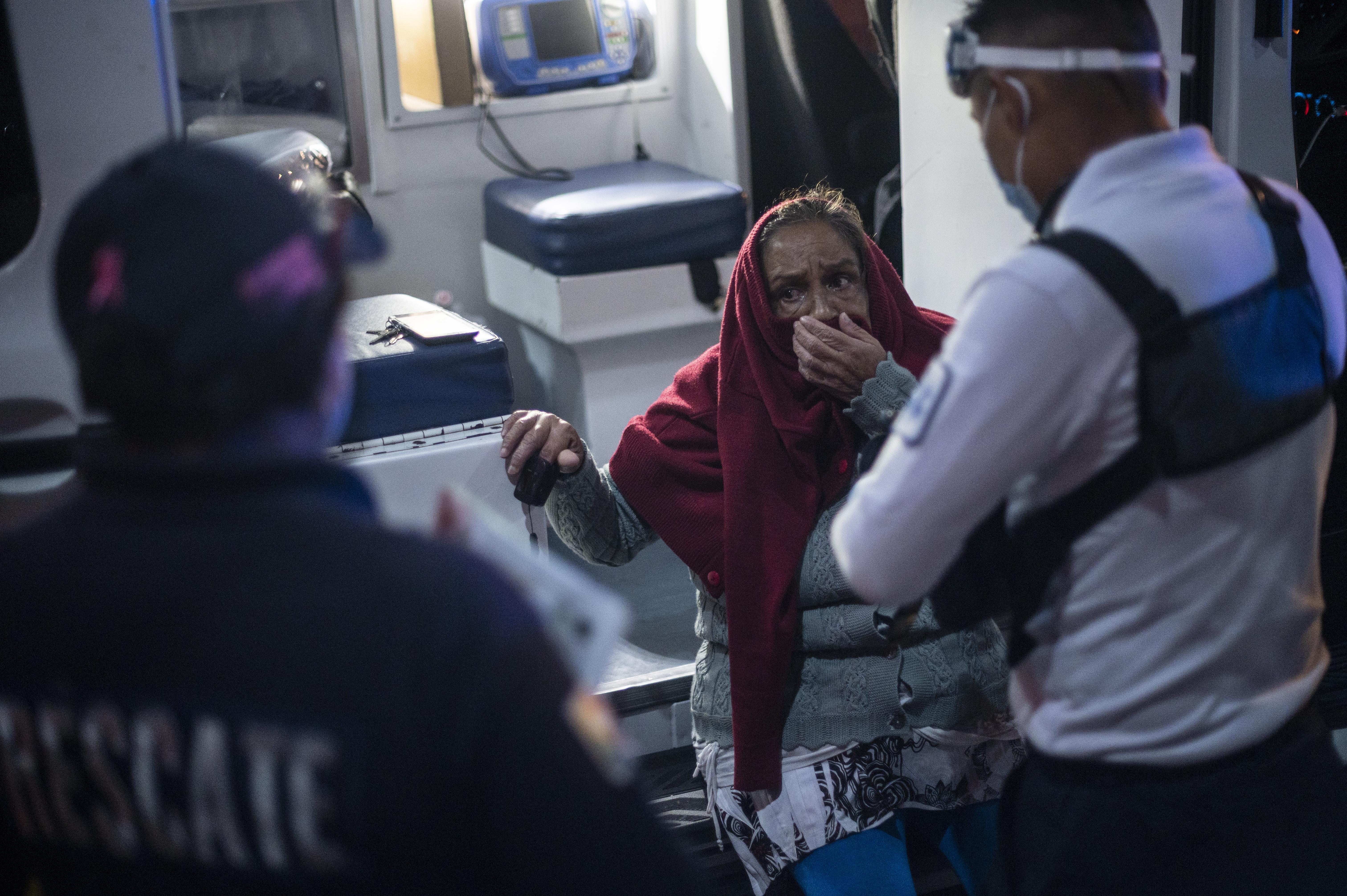 El paramédico Jesús Sholndick, de 29 años, (D) revisa a una anciana con problemas de presión arterial en Ciudad Nezahualcóyotl, Estado de México, México, el 18 de junio de 2020 durante la nueva pandemia de coronavirus COVID-19. (Foto por Pedro PARDO / AFP)