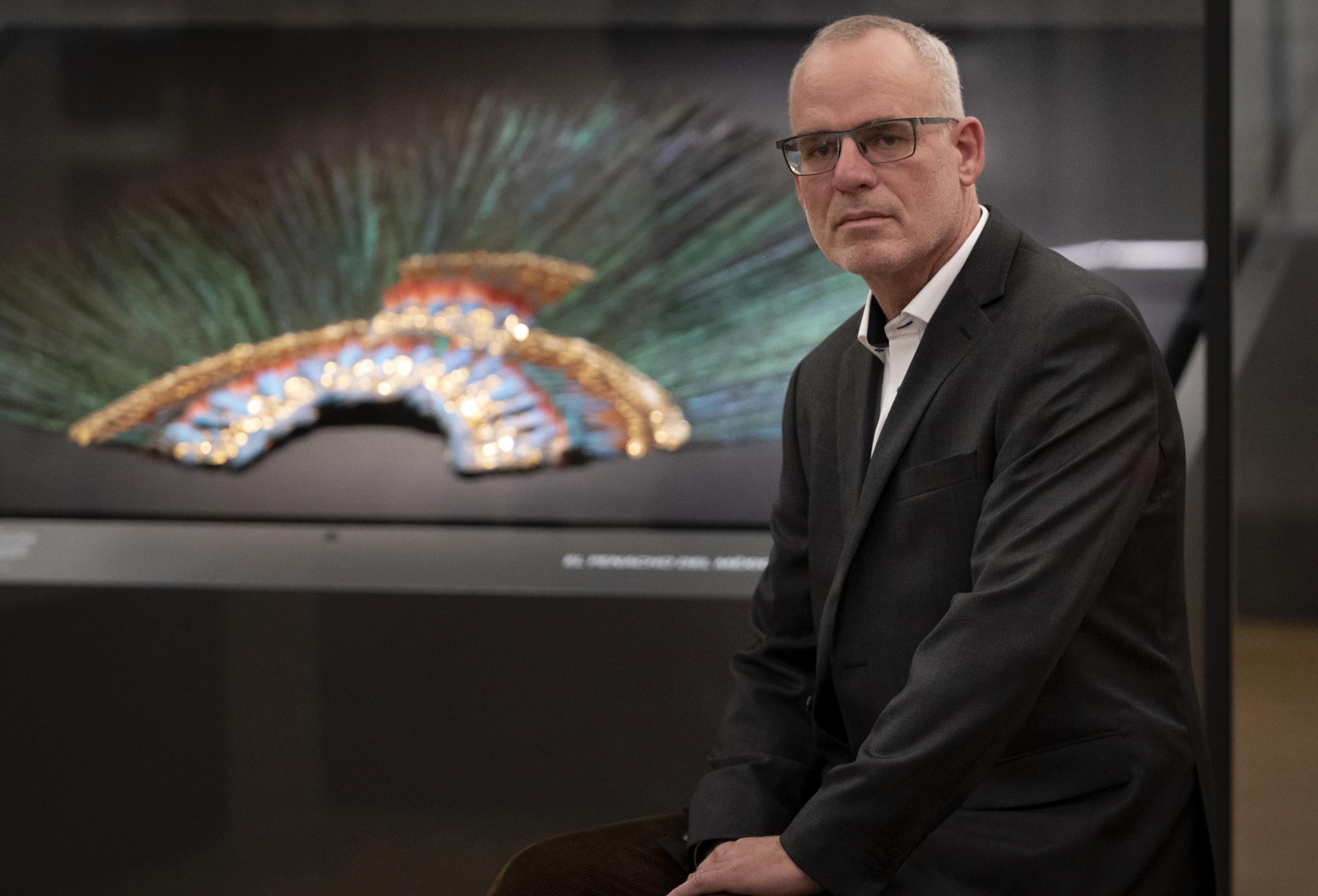 Gerard van Bussel, curador del departamento de América del Norte y Central en el Weltmuseum Wien, frente al stand del Penacho. (Foto: Joe Klamar / AFP)
