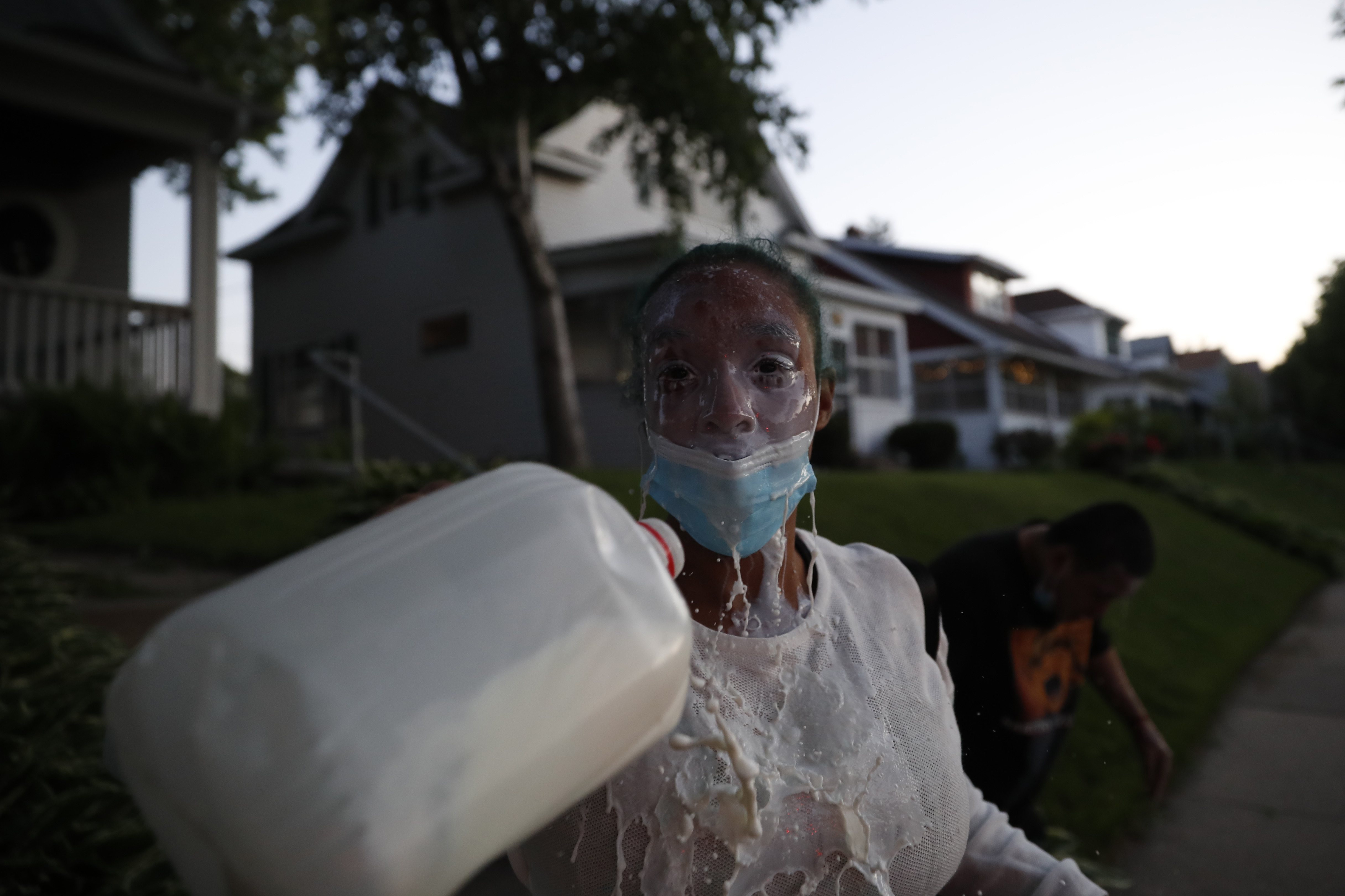 Una manifestante se lava los ojos con leche en St. Paul, Minnesota (AP Photo/John Minchillo)