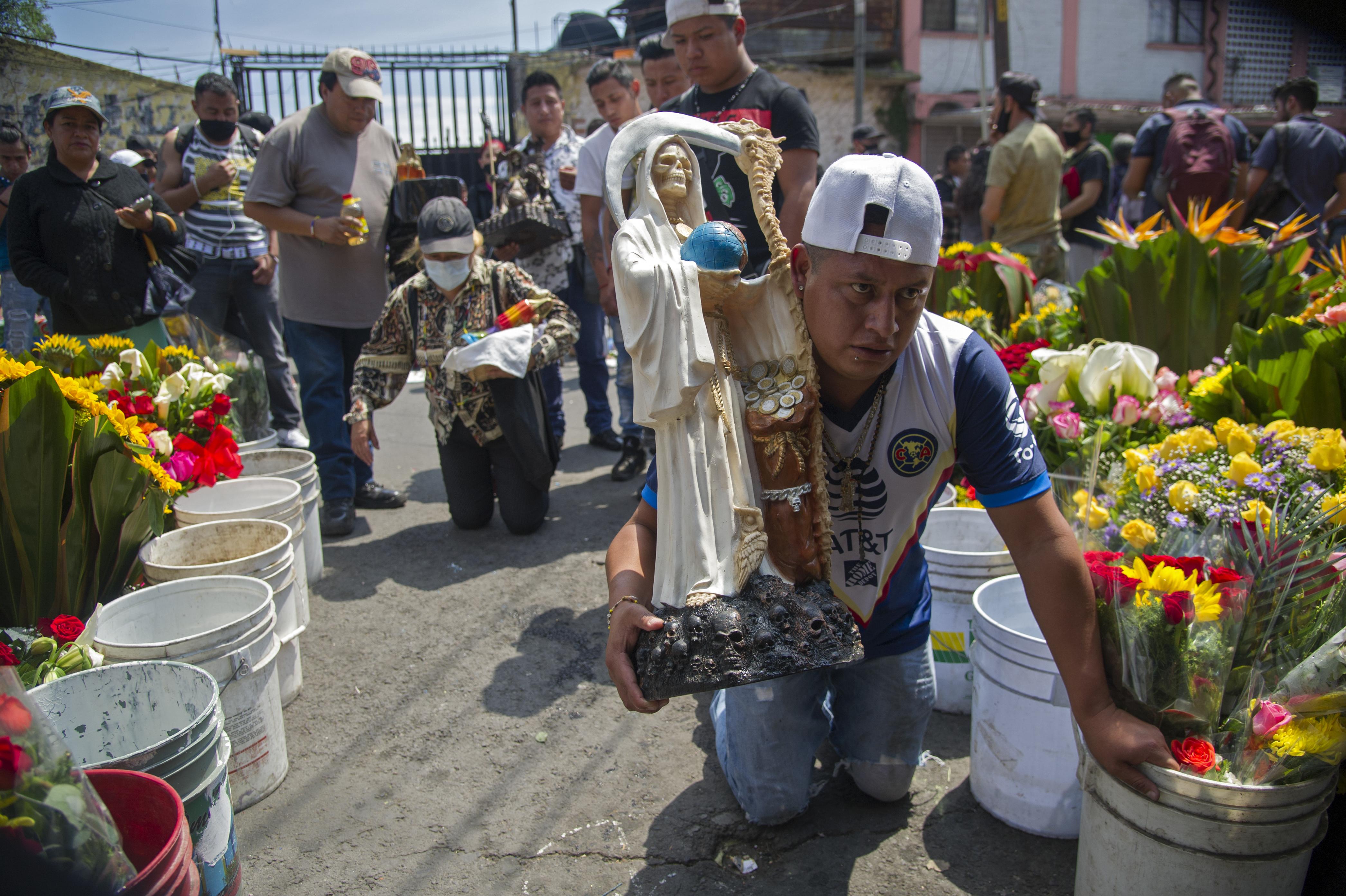 Un hombre camina de rodillas portando una figura de Santa Muerte frente a su santuario en la calle Alfarería, en el barrio Tepito, de la Ciudad de México, el 1 de octubre de 2020