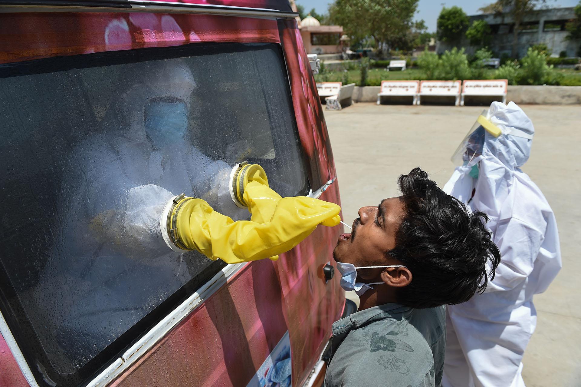 Un funcionario de salud utiliza un hisopo para recoger una muestra de un hombre para la prueba de COVID-19 desde el interior de una furgoneta móvil en la aldea de Changodar, a unos 20 kms de Ahmedabad, el 23 de abril de 2020. (Foto de SAM PANTHAKY / AFP)