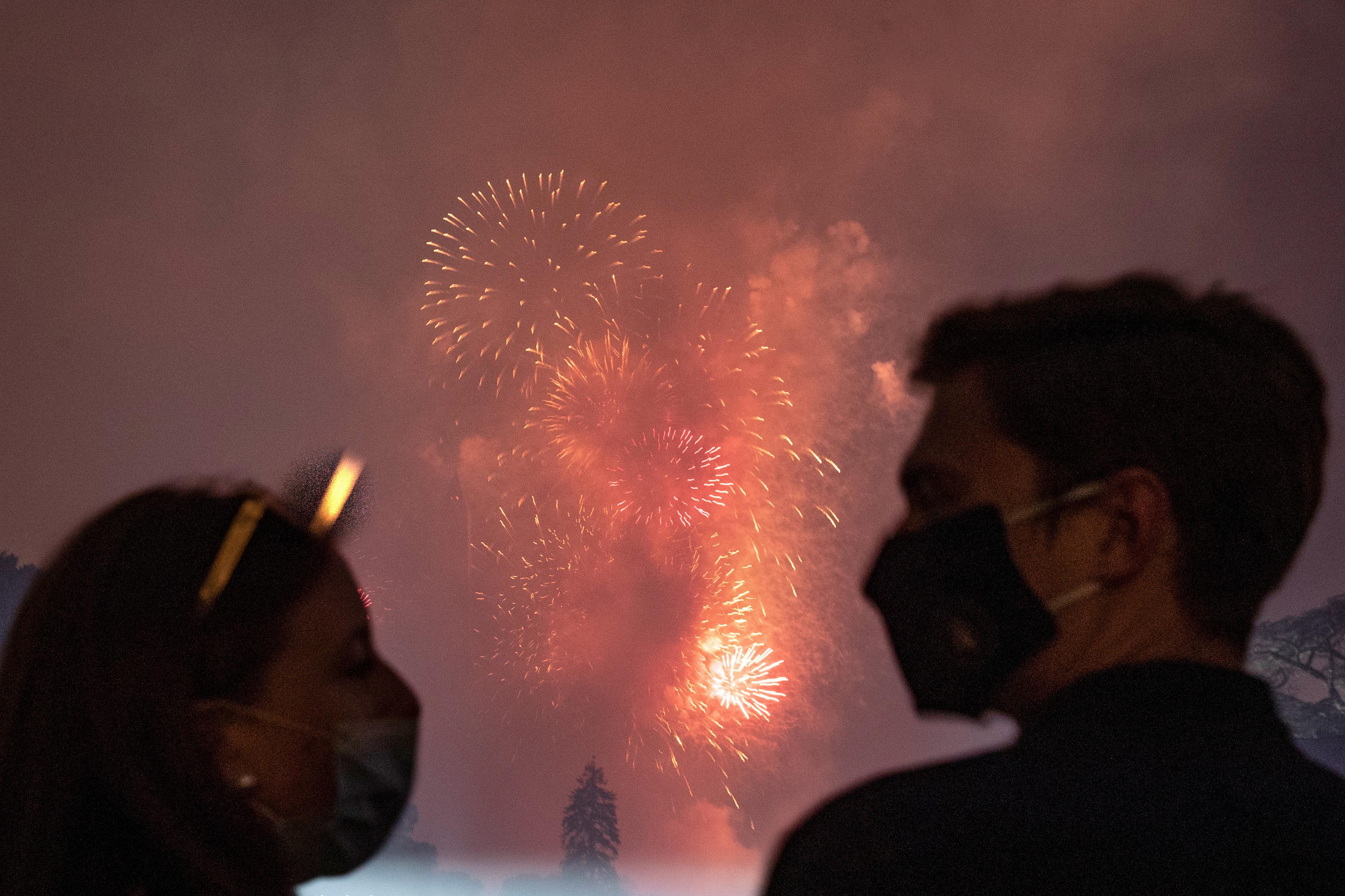 Una pareja se mira utilizando tapabocas mientras se ven los fuegos artificiales al fondo