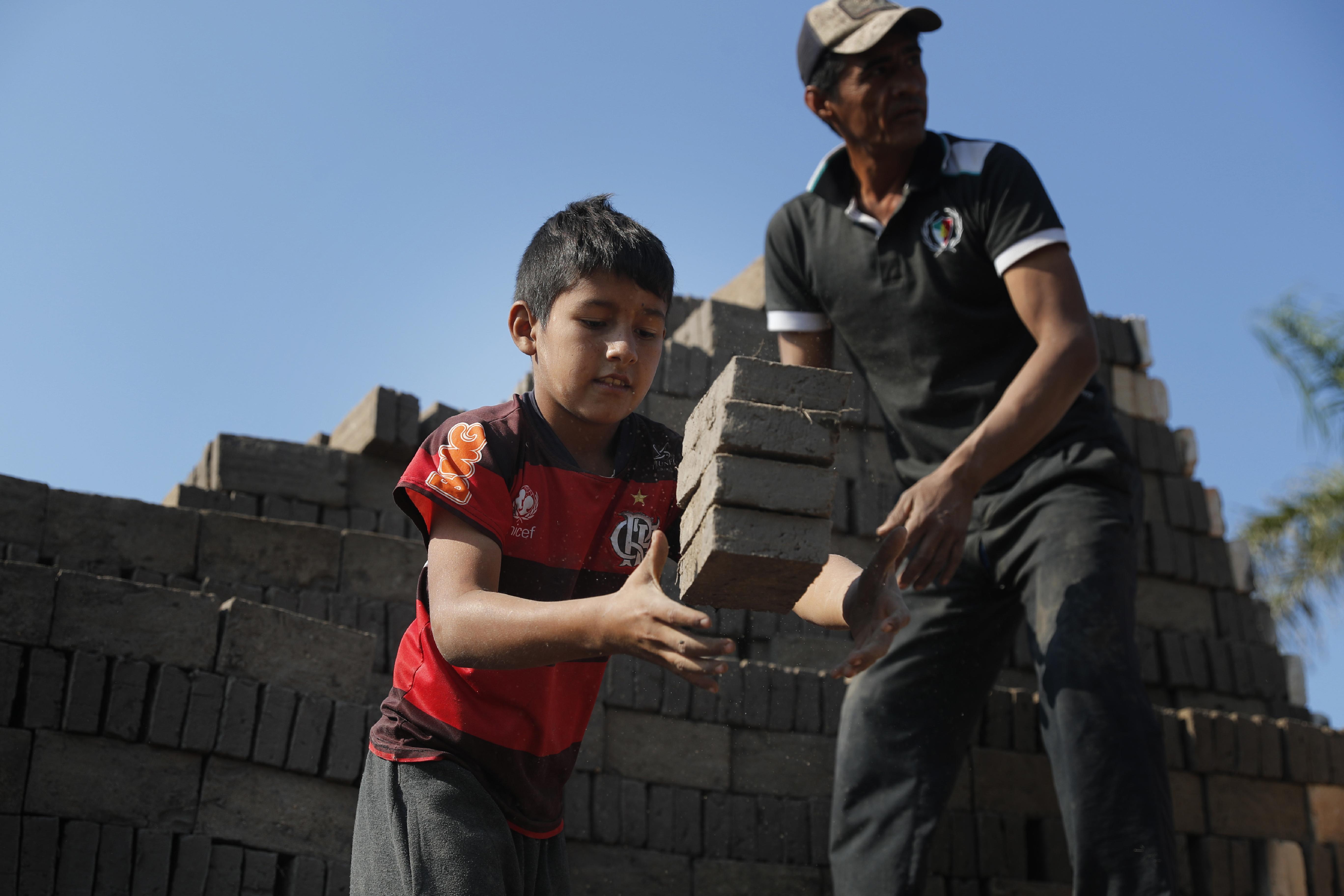 Alejandro, de 9 años, atrapa ladrillos para entregárselos a un hombre que los mete en el horno en una fábrica de ladrillos dirigida por sus tíos en Tobati, Paraguay, el lunes 31 de agosto de 2020.