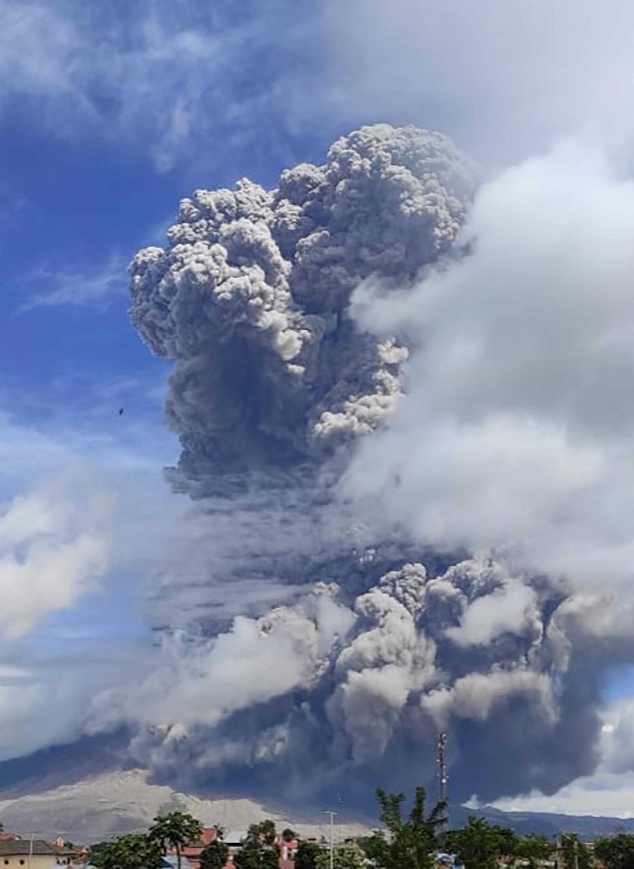 Más lejos, en Berastagi, una ciudad turística en la provincia de Sumatra del Norte, a unos 20 kilómetros (12,4 millas) del cráter, los automovilistas encendieron los faros durante el día para poder ver entre la ceniza. (MUHAMAD NURUL ASRORI / Centre for Investigation and Technology Development of Geological Disaster / AFP)