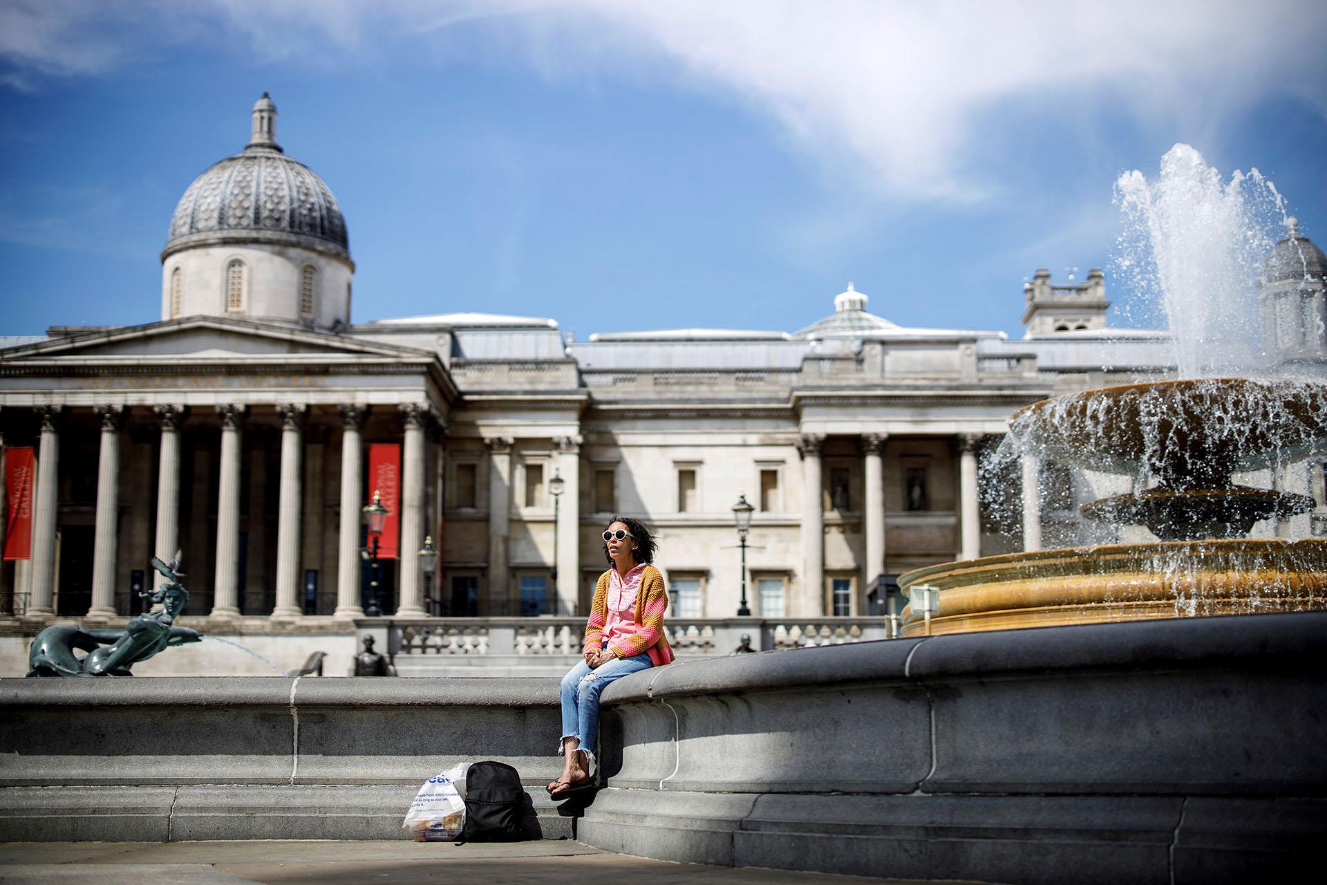 Una mujer disfruta del sol en la Trafalgar Square de Londres.