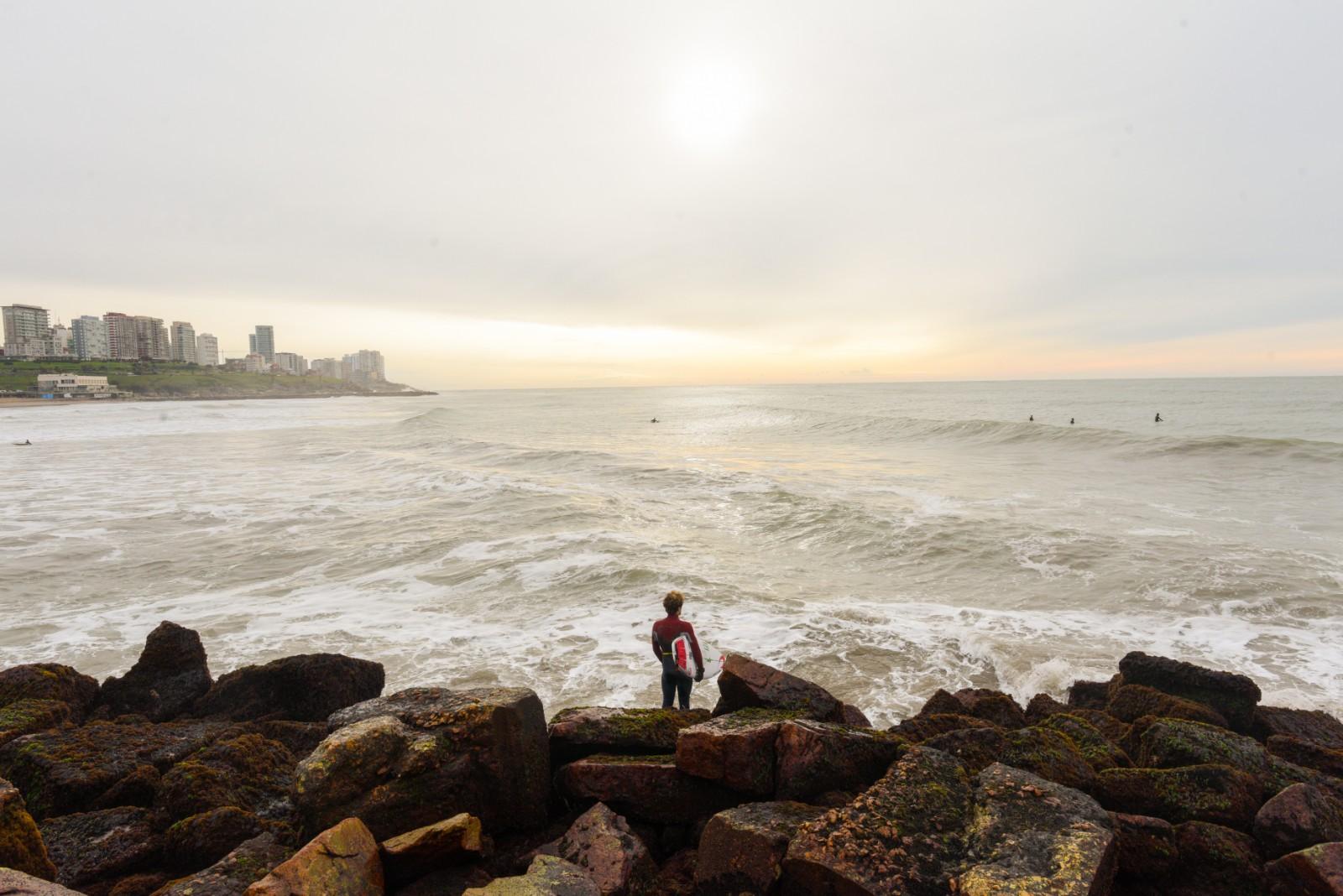 Allá en el mar, un grupo de surfers disfruta de su pasión. Otro mira el amanecer desde las rocas. Mar del Plata espera que lleguen 21 días sin contagios para entrar en Fase 5.