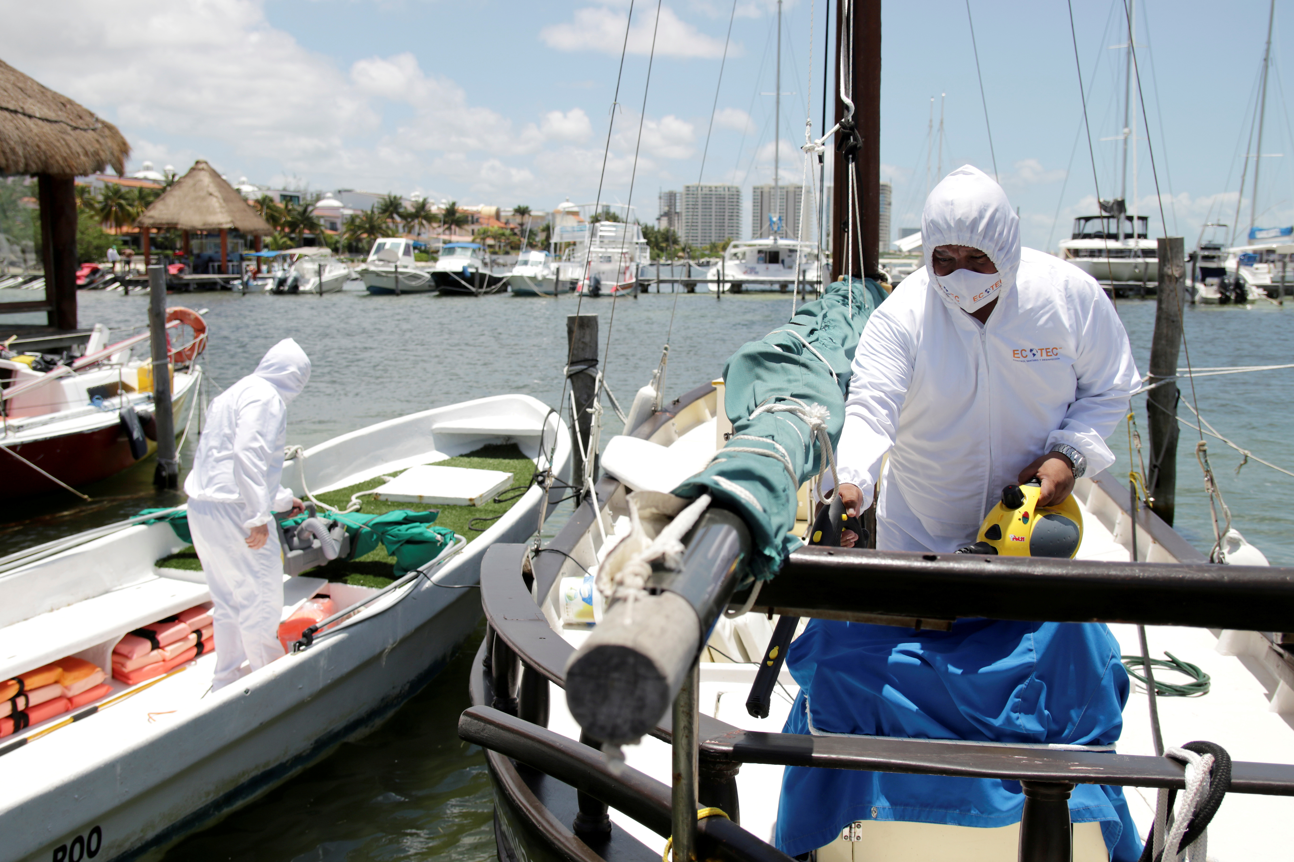 Los empleados de una empresa privada desinfectan los barcos en un puerto deportivo después de que las autoridades locales impusieron estrictas medidas sanitarias para reabrir gradualmente a pesar de la pandemia de la enfermedad por coronavirus (COVID-19), en Cancún, México, 10 de junio de 2020. Fotografía tomada el 10 de junio de 2020. Foto: Reuters.