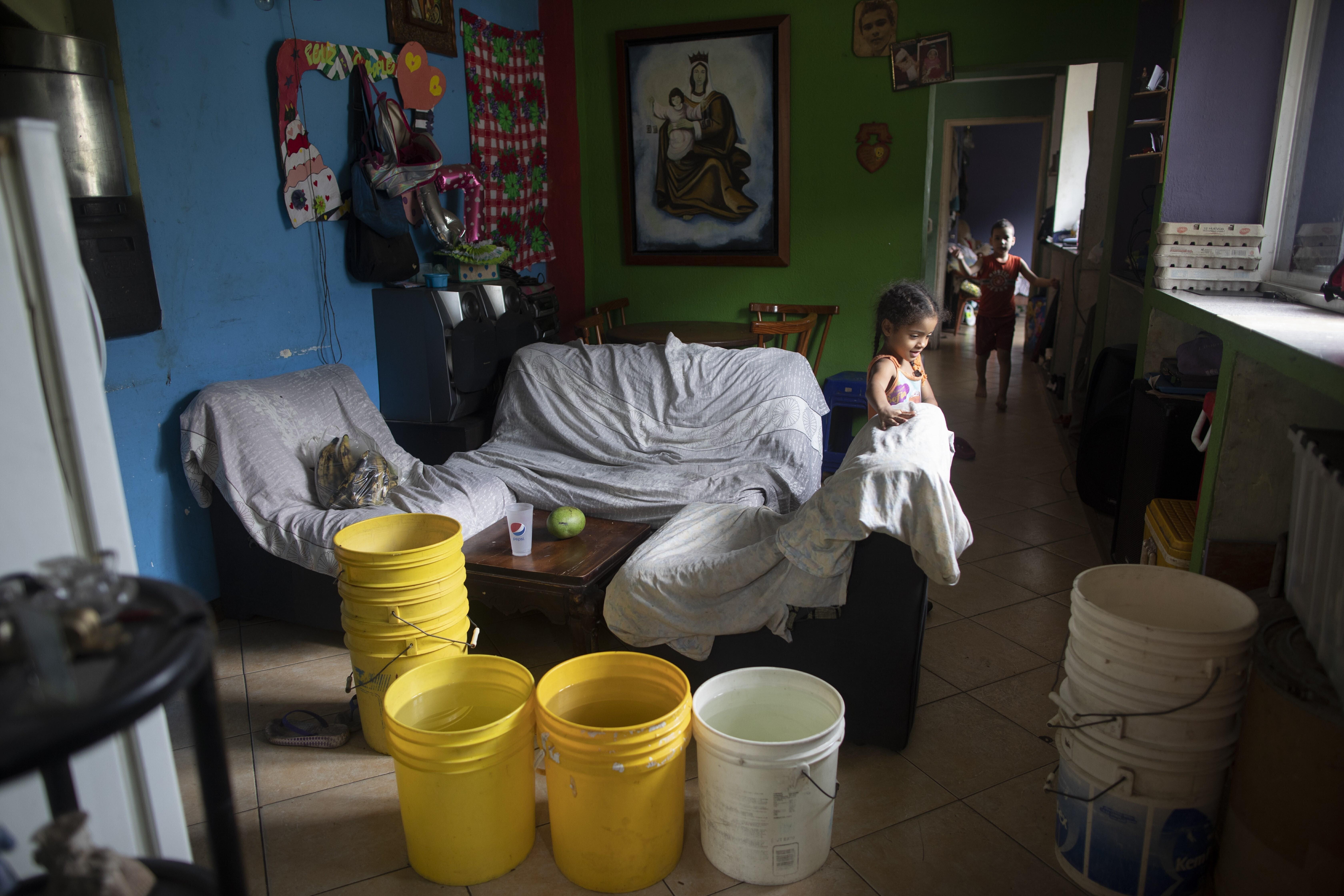 Varios cubos, algunos de ellos llenos con agua proporcionada por un camión cisterna gubernamental, en la sala de estar de una casa en el vecindario de Petare, en Caracas, Venezuela, el 15 de junio de 2020. El colapso económico de Venezuela ha dejado a la mayoría de los hogares sin un suministro de agua corriente confiable. (AP Foto/Ariana Cubillos)