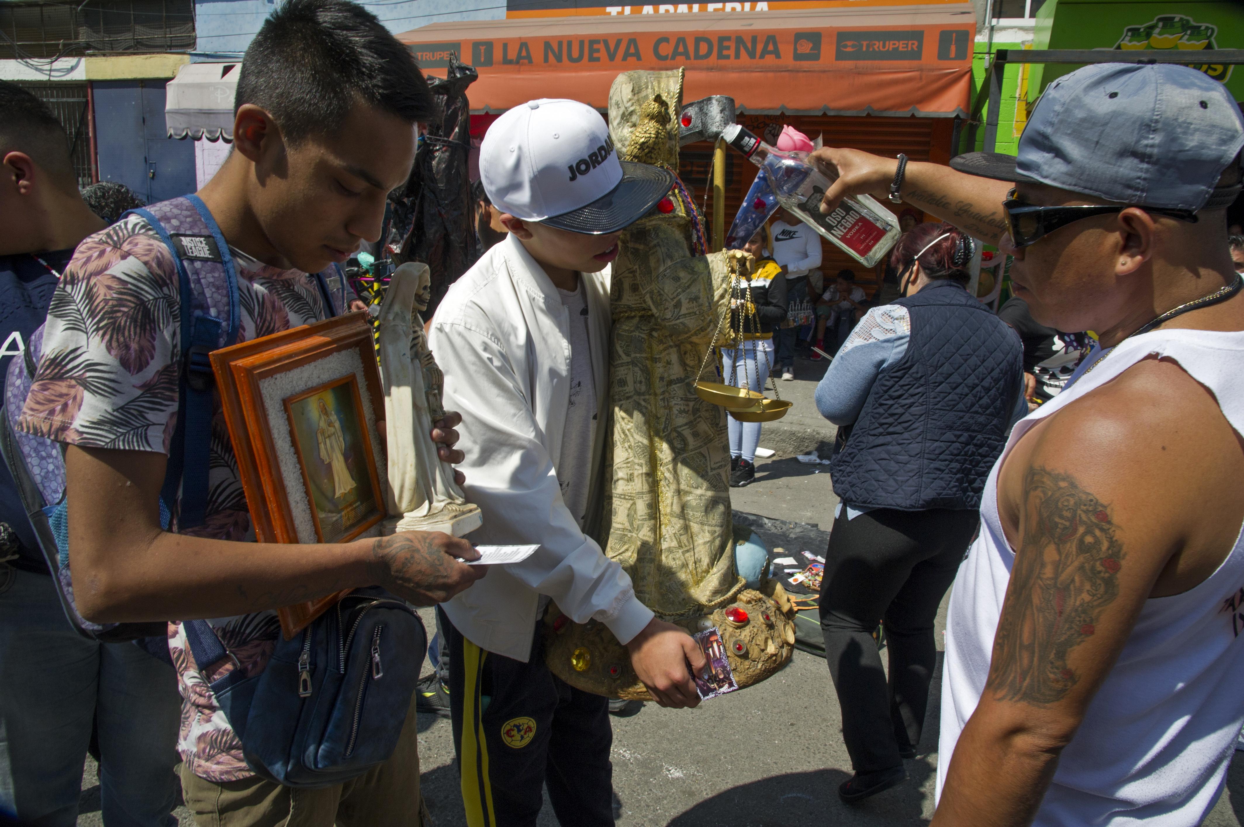 Un hombre rocía alcohol etílico sobre una figura de Santa Muerte como ritual de limpieza cerca de su santuario en la calle Alfarería, en el barrio de Tepito, de la Ciudad de México, el 1 de octubre de 2020