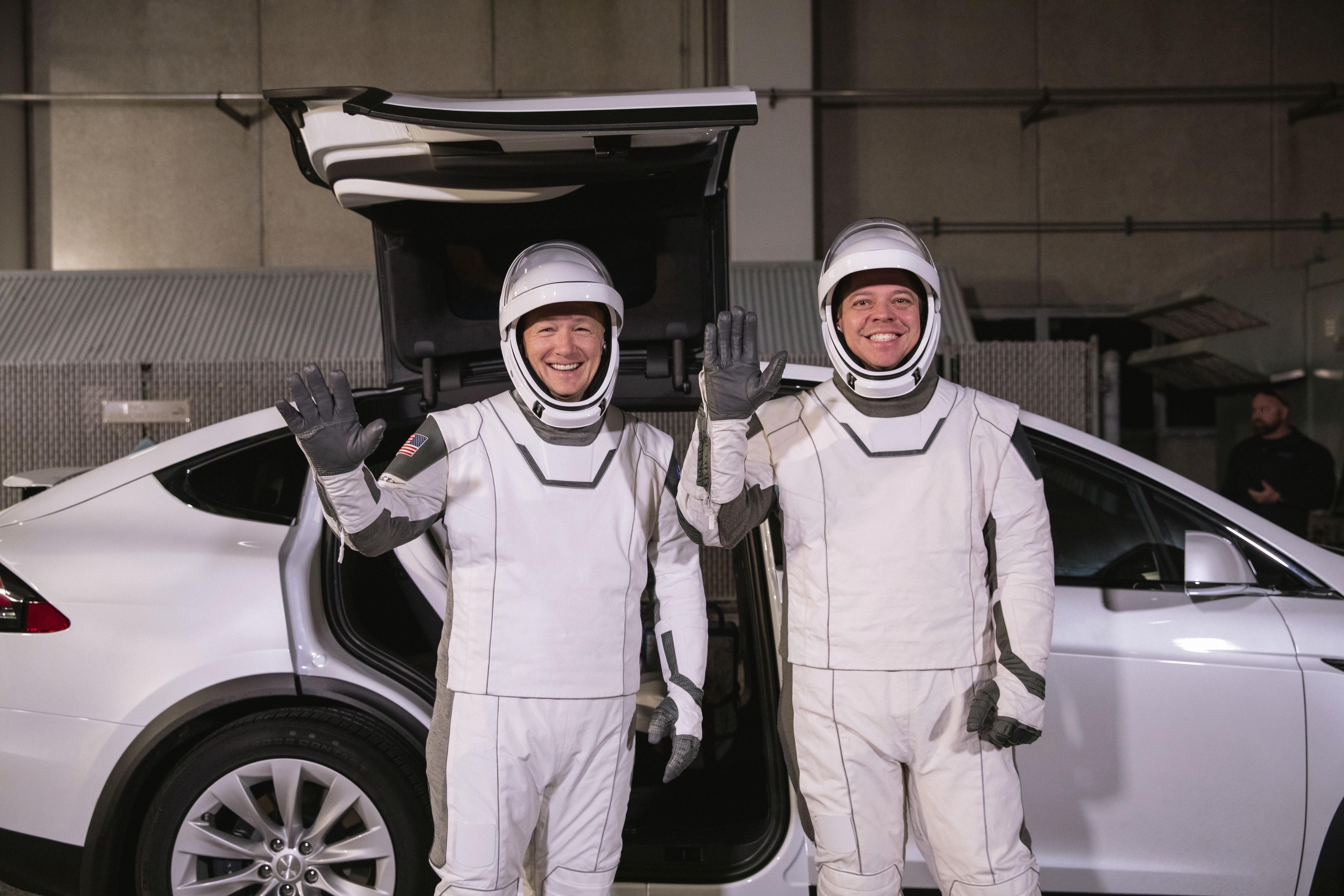 En esta fotografía del viernes 17 de enero de 2020 proporcionada por la NASA, los astronautas Doug Hurley (izquierda) y Robert Behnken posan frente al automóvil eléctrico Model X de Tesla durante un ensayo de lanzamiento en el Centro Espacial Kennedy, en Cabo Cañaveral, Florida. (Kim Shiflett/NASA vía AP)