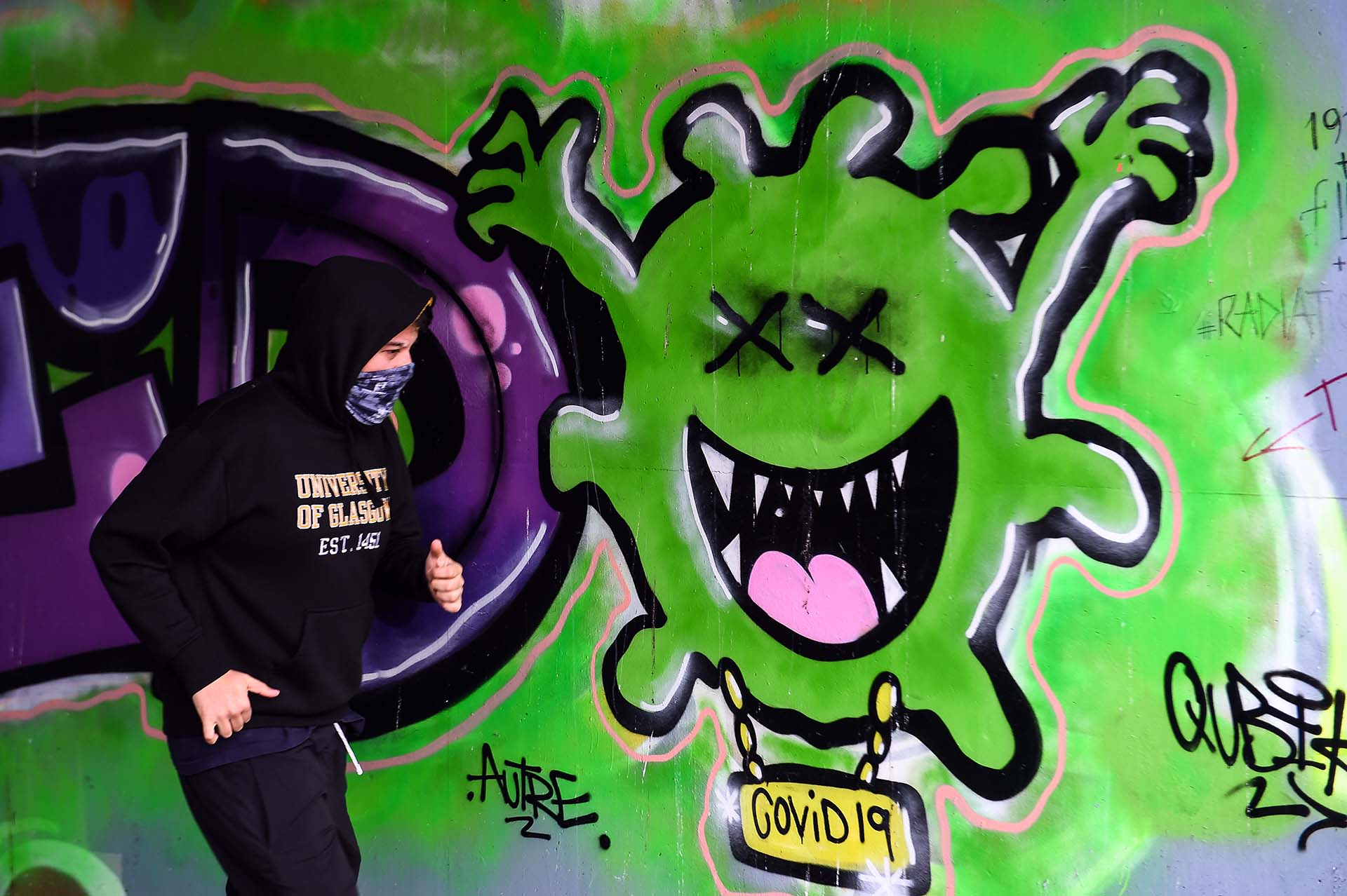 Un corredor pasa frente aun grafitti del coronavirus en una pared de Glasgow en Escocia.