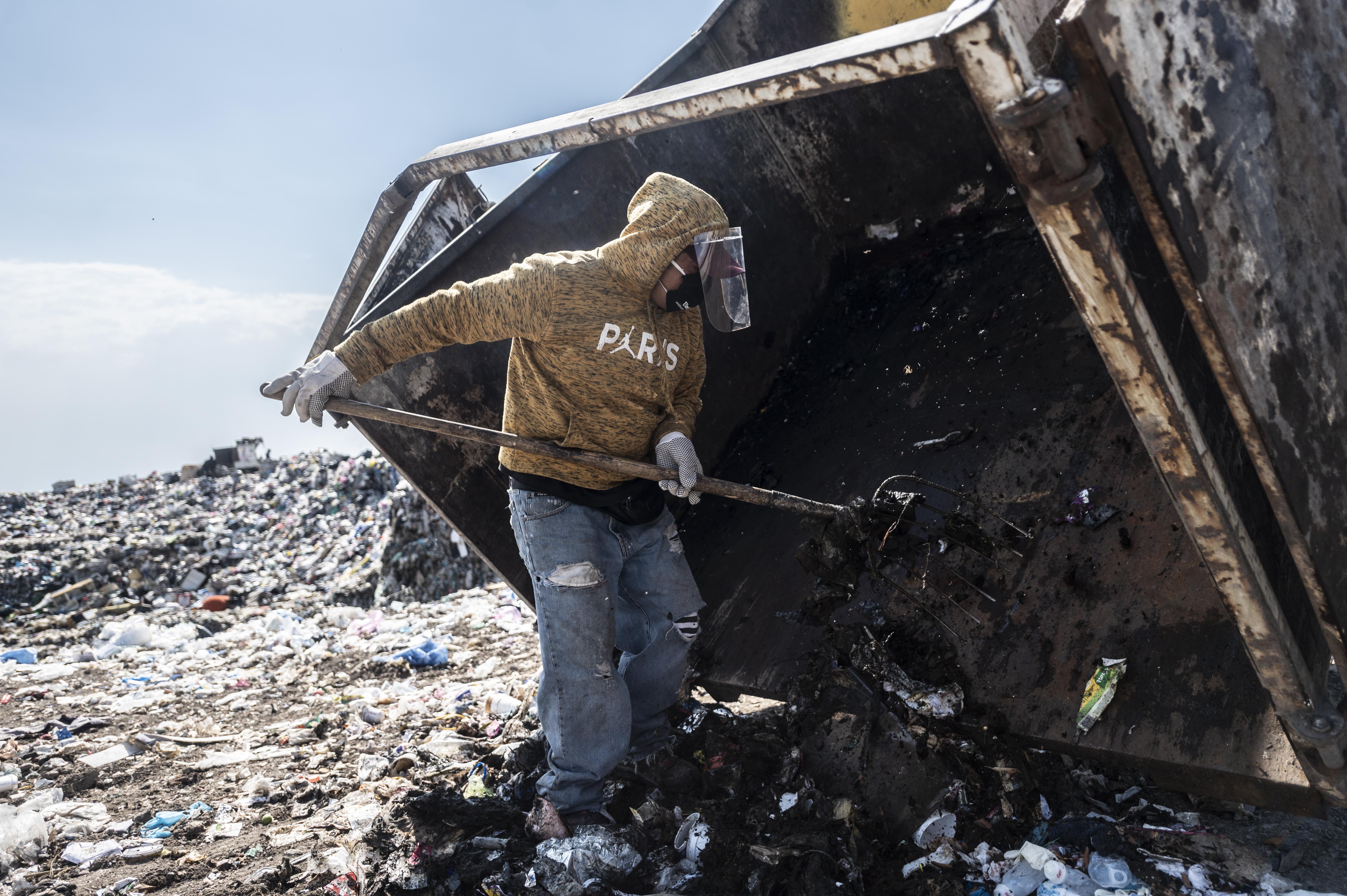 Un recolector de basura descarga desechos médicos en el basurero
