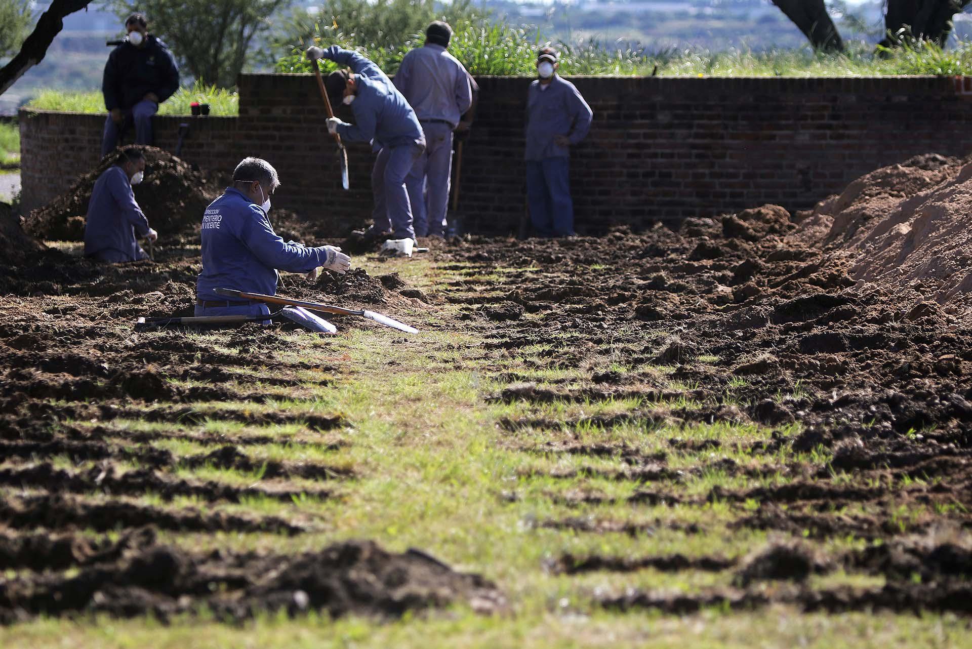 En pleno aumento de los casos, operarios cavan tumbas en el cementerio de San Vicente, en la provincia de Córdoba