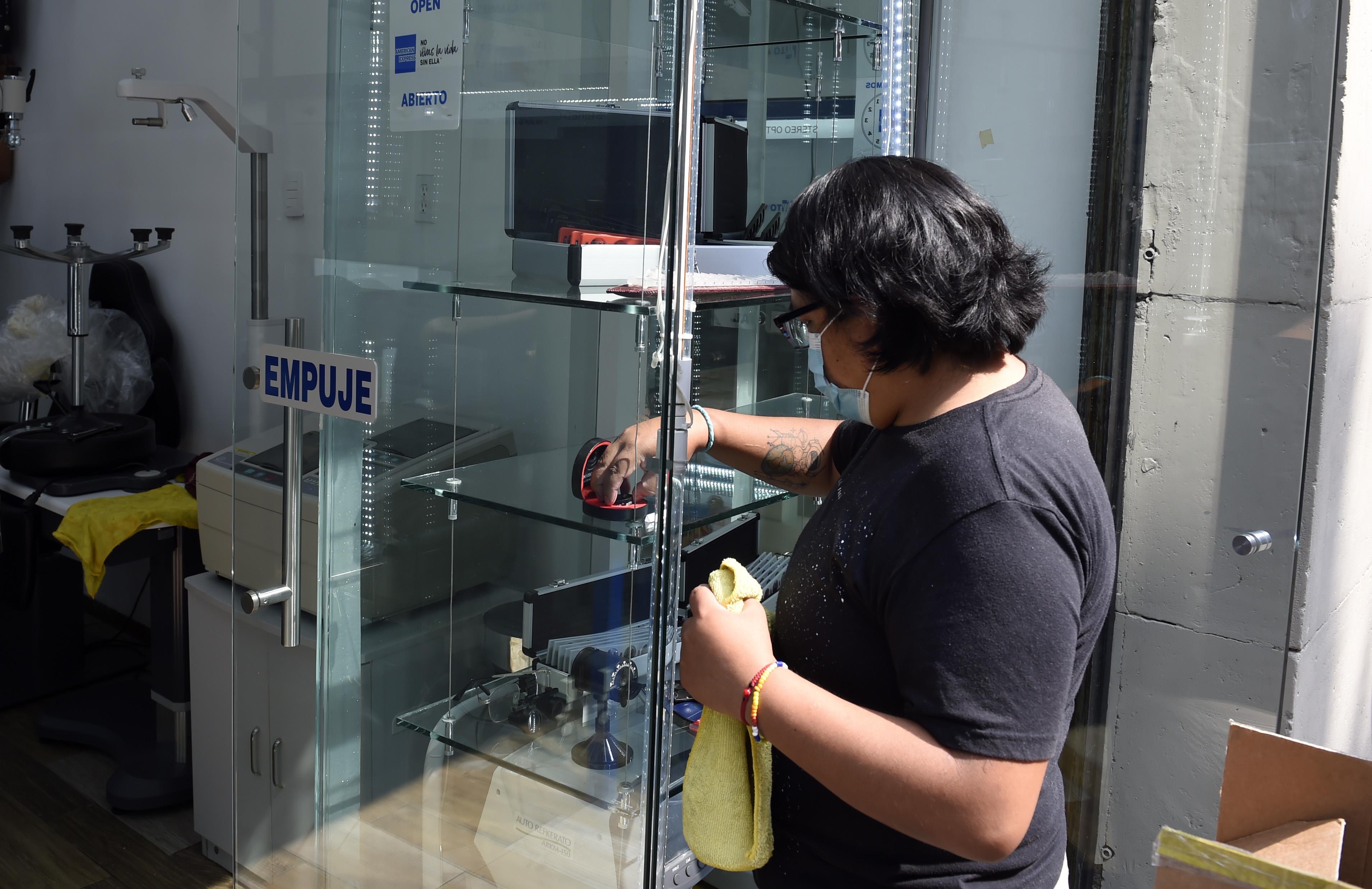 El empleado de una óptica limpia antes de volver a abrir en la Ciudad de México el 29 de junio de 2020 durante la pandemia de COVID-19.(Foto: ALFREDO ESTRELLA / AFP)