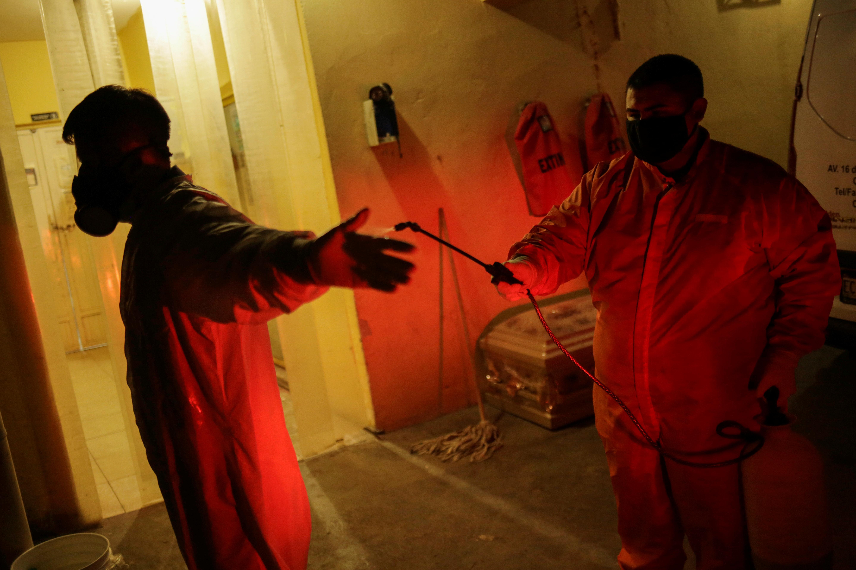 Los empleados de la funeraria Ríos se someten a desinfección en sus instalaciones luego de retirar el cuerpo de un hombre, que murió por coronavirus (COVID-19), en Ciudad Juárez, México, el 23 de octubre de 2020.