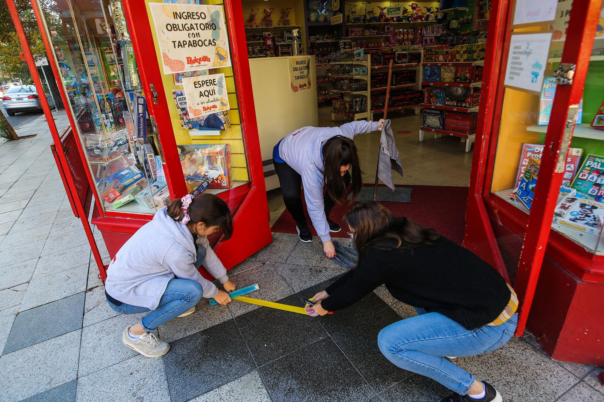 Empleadas de un comercio pegan una banda amarilla en el suelo para indicar hasta dónde se podían acercar los clientes, que entrarían en turnos (Christian Heit)