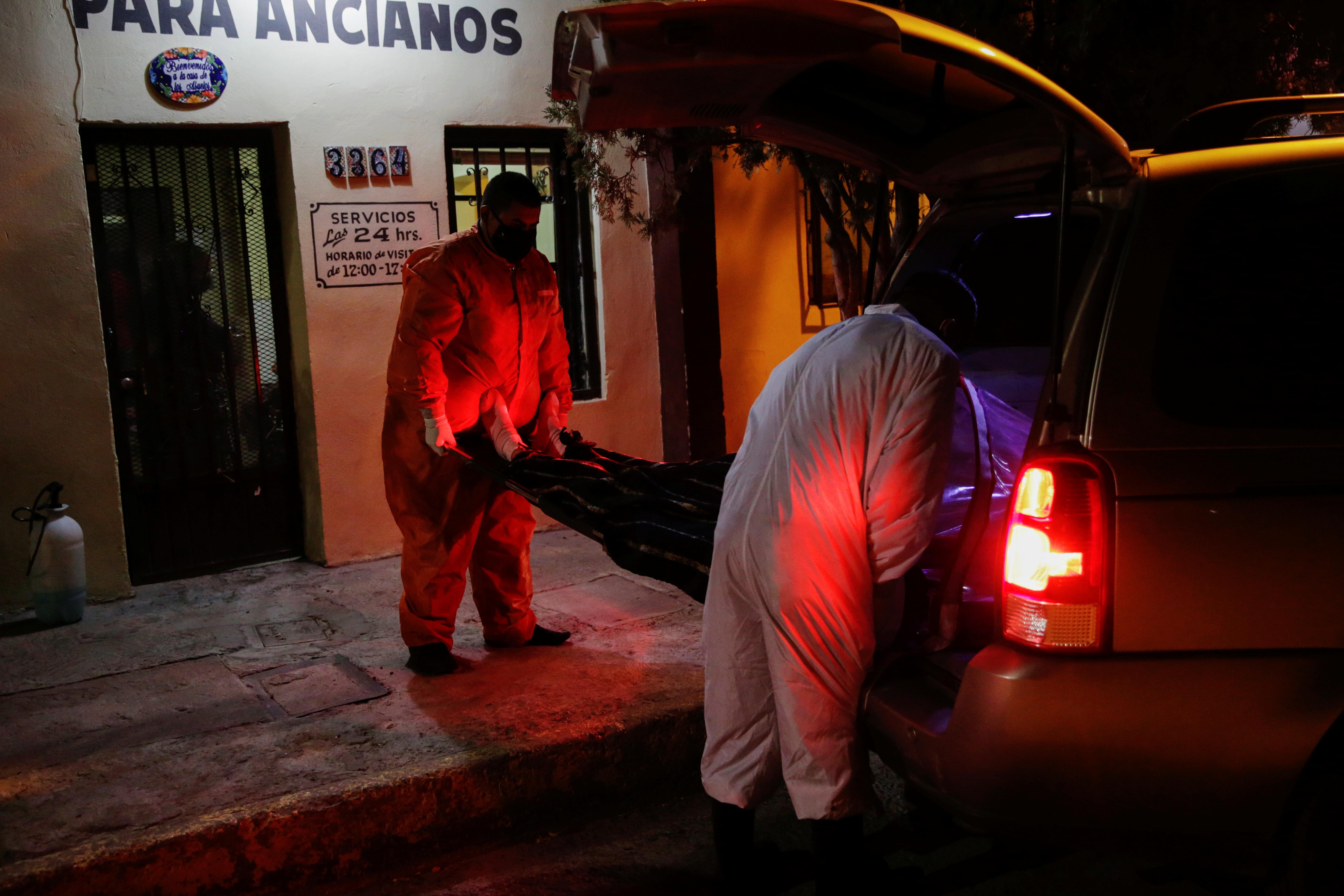 Empleados de la funeraria Ríos cargan el cuerpo de un hombre, que murió a causa COVID-19, para trasladarlo a una funeraria en Ciudad Juárez, México, el 23 de octubre de 2020.